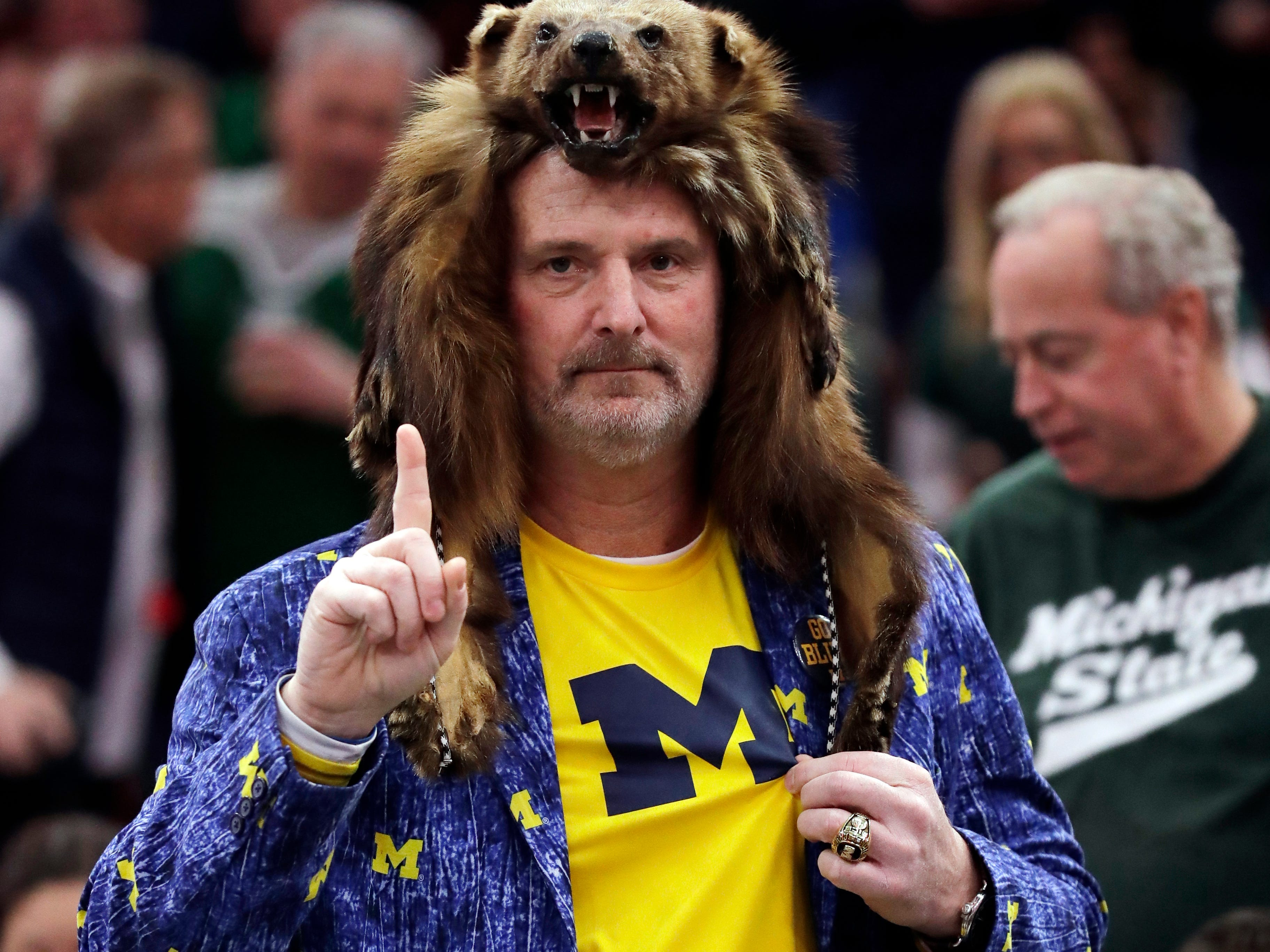 A Michigan fan cheers before an NCAA college basketball championship game between Michigan State and Michigan in the Big Ten Conference tournament, Sunday, March 17, 2019, in Chicago.
