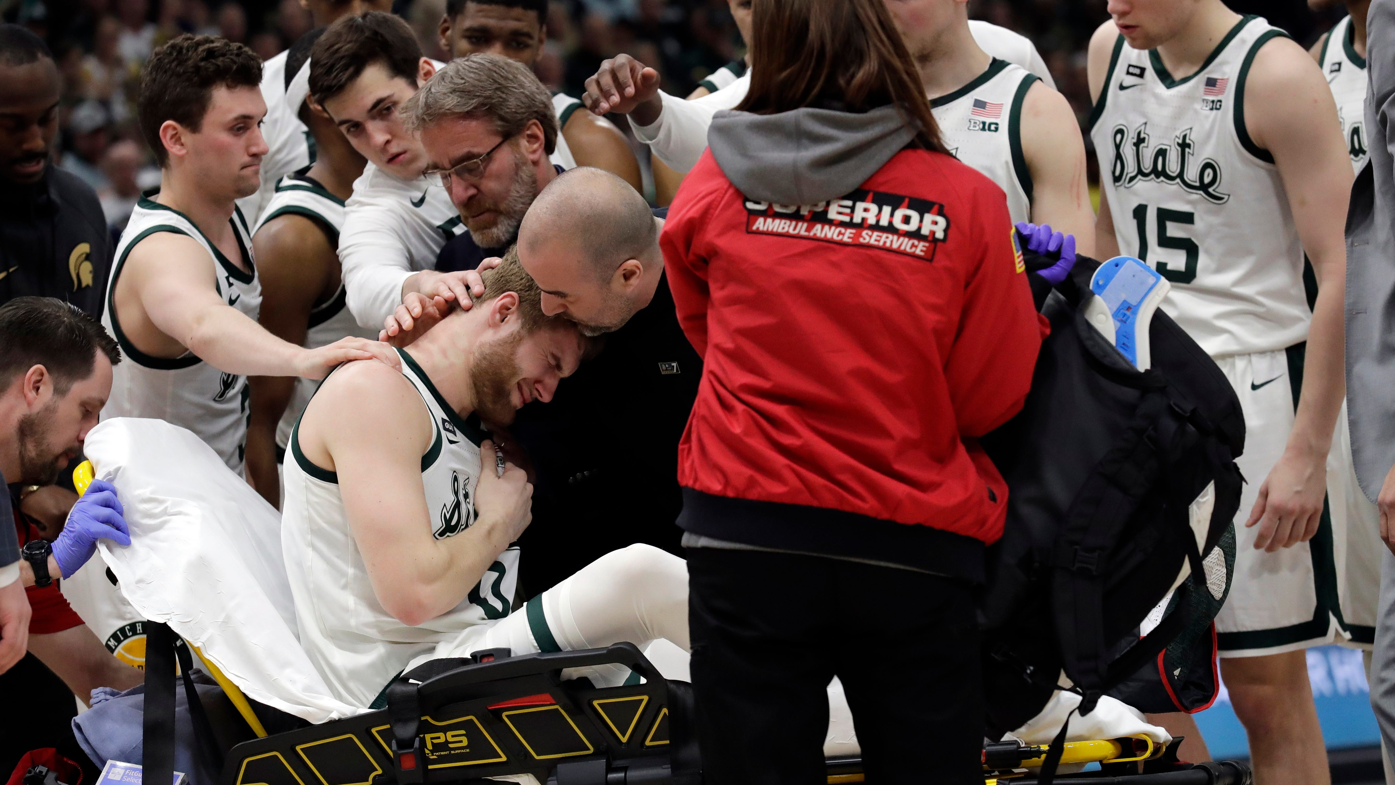 Michigan State players gather as Kyle Ahrens (0)...