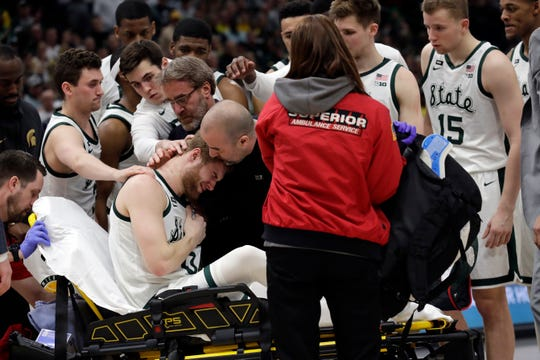 Michigan State athletic trainer Nick Richey (middle) consoles injured basketball player Kyle Ahrens (0) after he's loaded onto a stretcher during the Big Ten Tournament Championship game Sunday, March 17, 2019, in Chicago.
