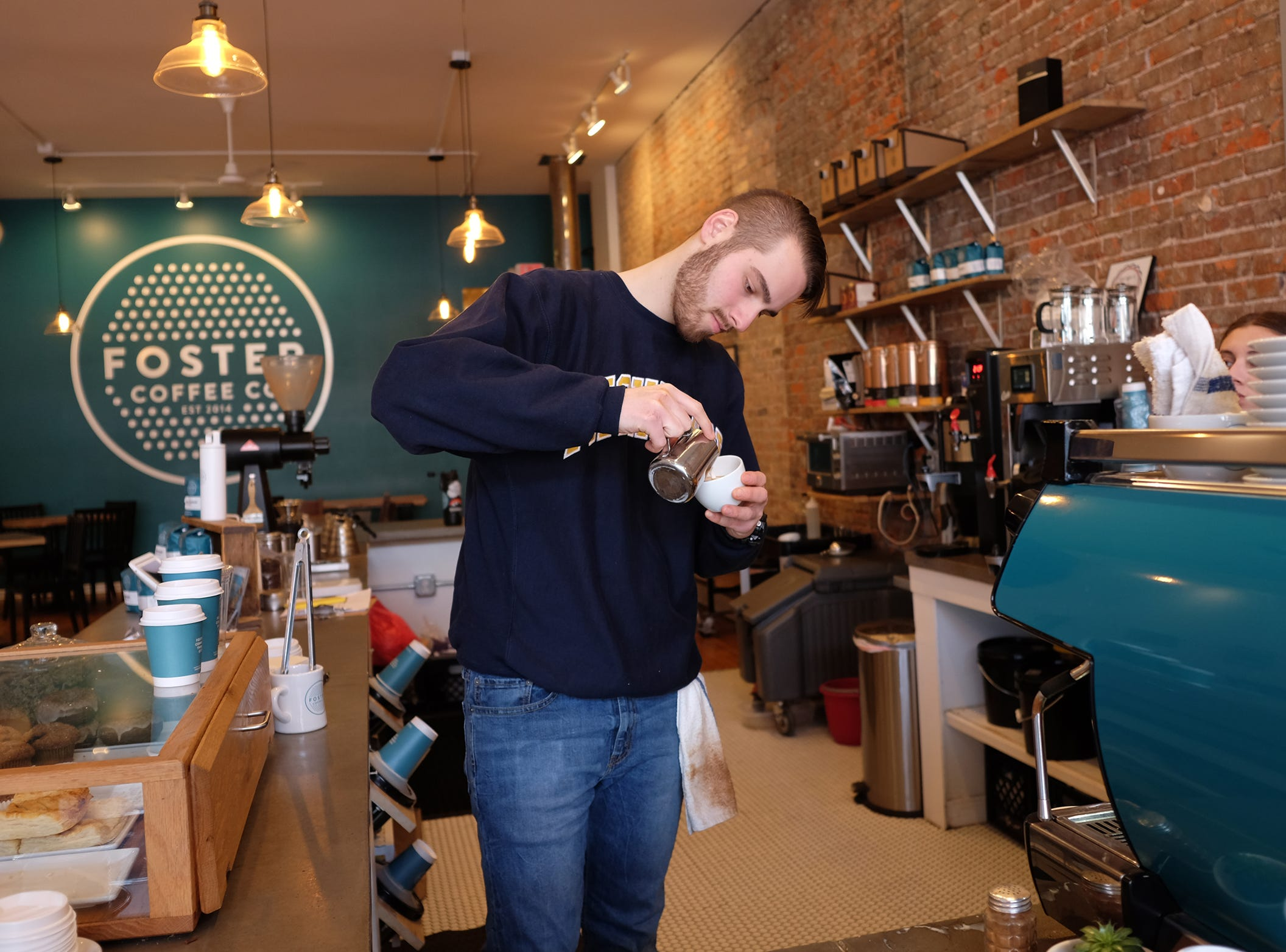 Barista Caleb Schlaack at Foster Coffee Company in Owosso carefully pours a cup.