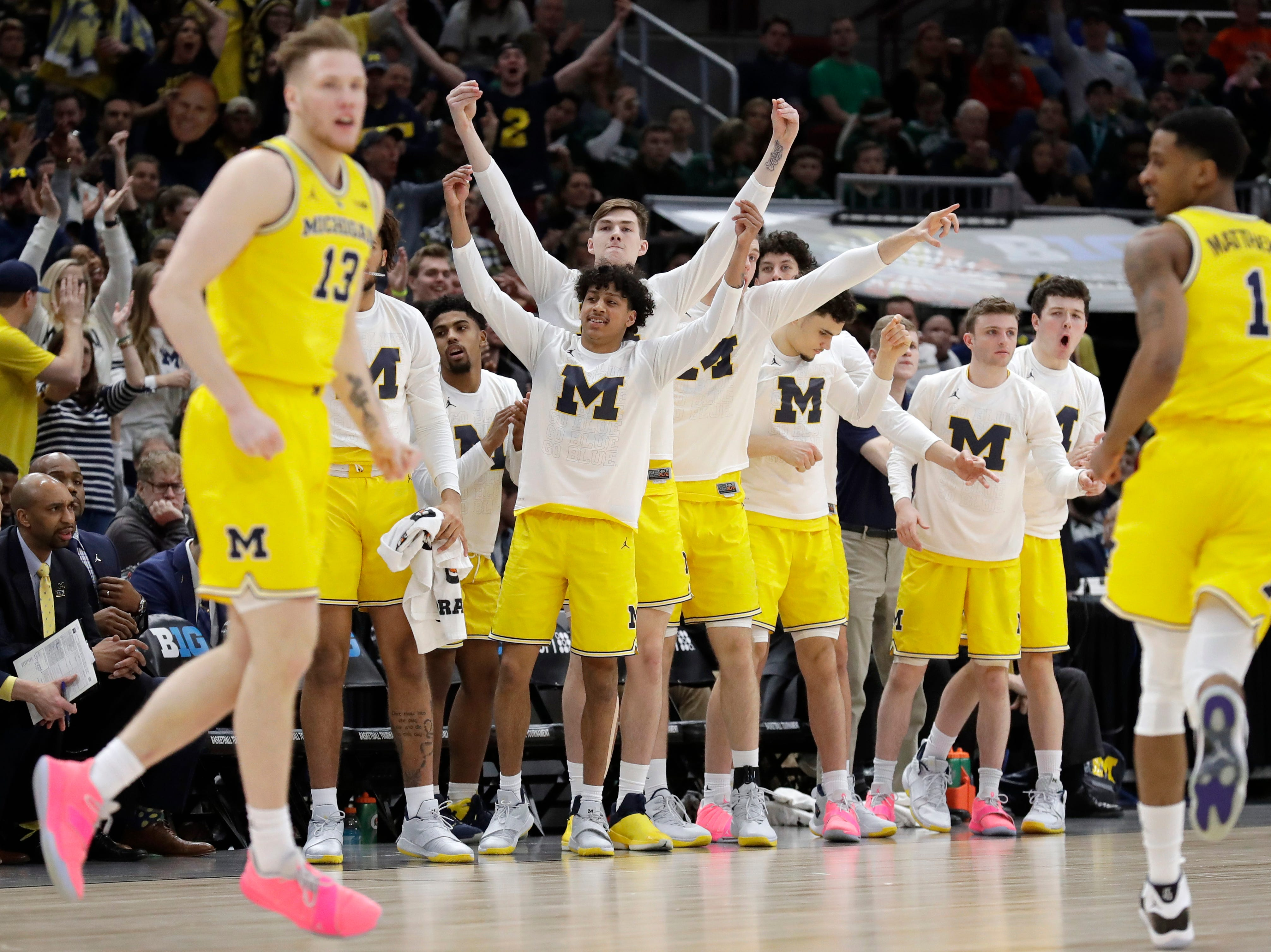 Michigan bench celebrate after Ignas Brazdeikis (13) shoots a 3-point basket during the first half of an NCAA college basketball championship game in the Big Ten Conference tournament, Sunday, March 17, 2019, in Chicago.