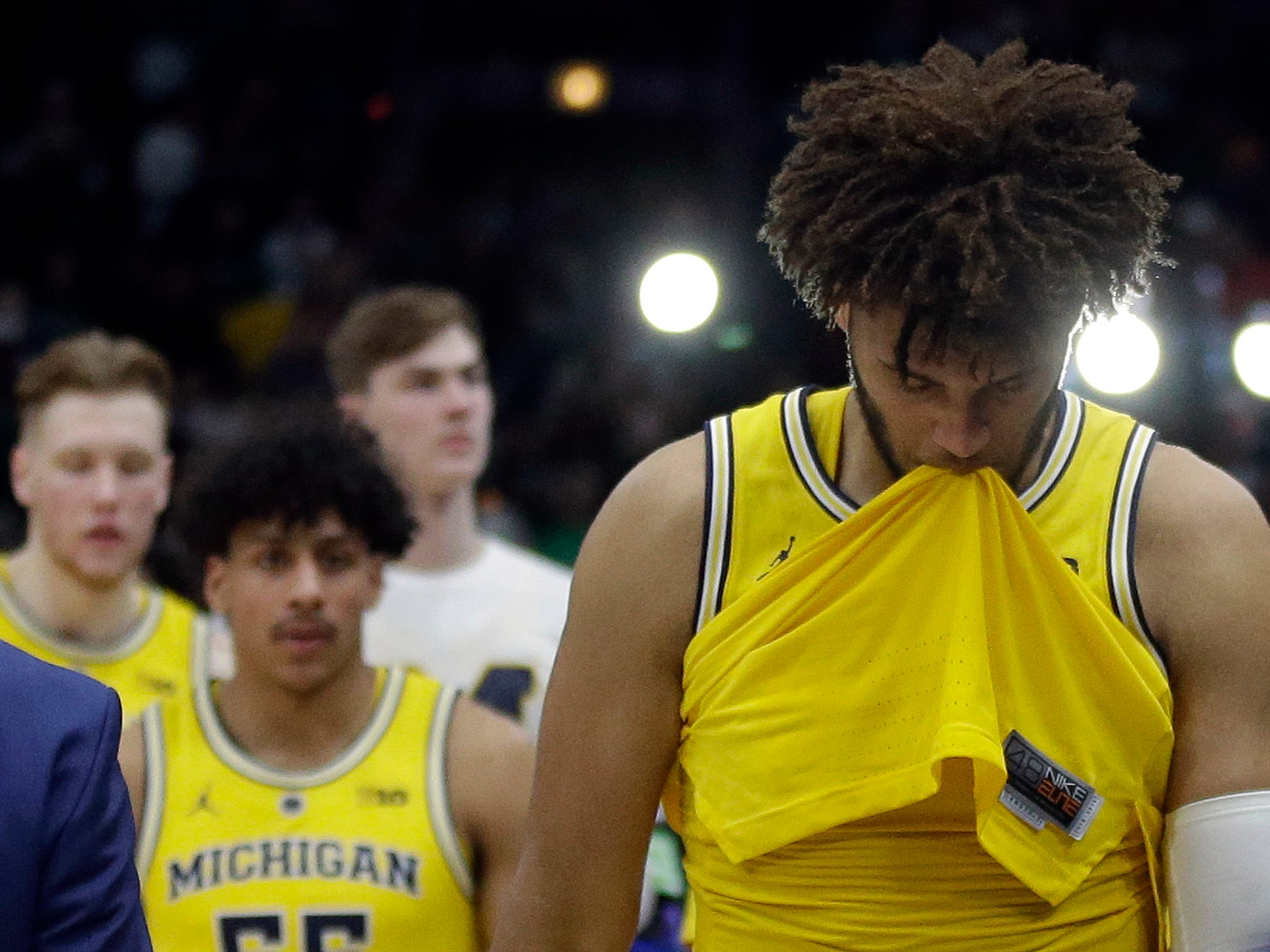 Michigan's Isaiah Livers, right looks down as he and his teammates walk off the court after the team's 65-60 loss to Michigan State in an NCAA college basketball championship game in the Big Ten Conference tournament, Sunday, March 17, 2019, in Chicago.