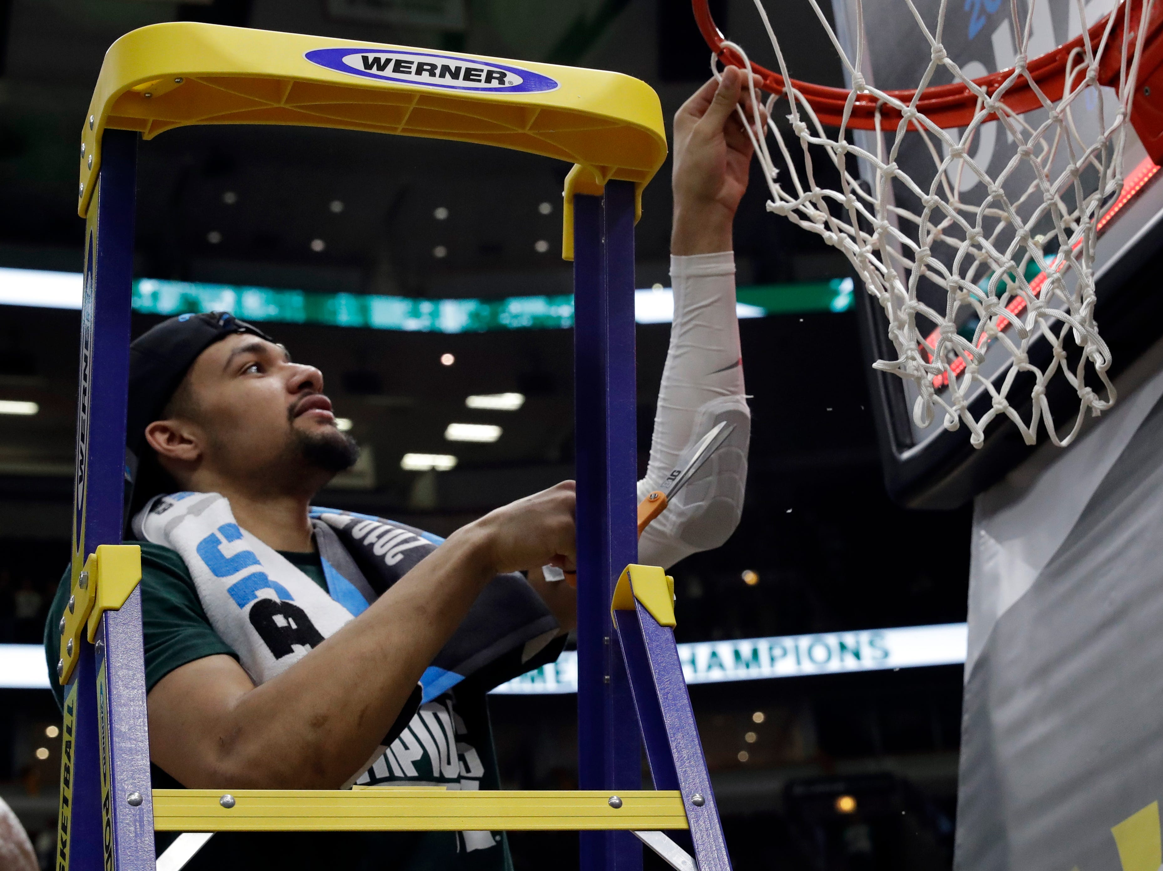 Michigan State's Kenny Goins cuts a piece of the net after defeating Michigan 65-60 in an NCAA college basketball championship game in the Big Ten Conference tournament, Sunday, March 17, 2019, in Chicago. (AP Photo/Nam Y. Huh)