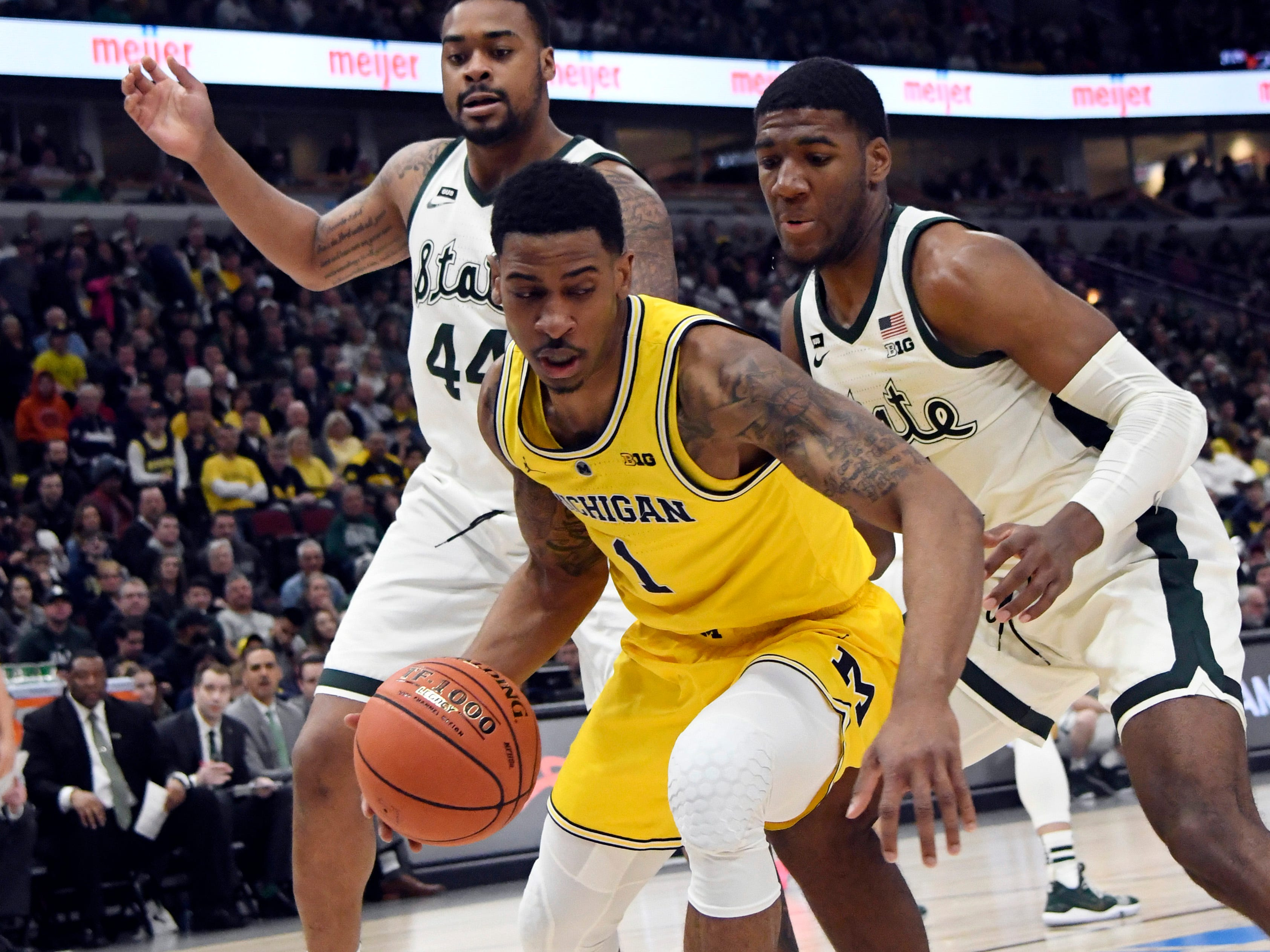 Michigan Wolverines guard Charles Matthews (1) is defended by Michigan State Spartans forward Nick Ward (44) and forward Aaron Henry (11) during the first half in the Big Ten conference tournament at United Center.