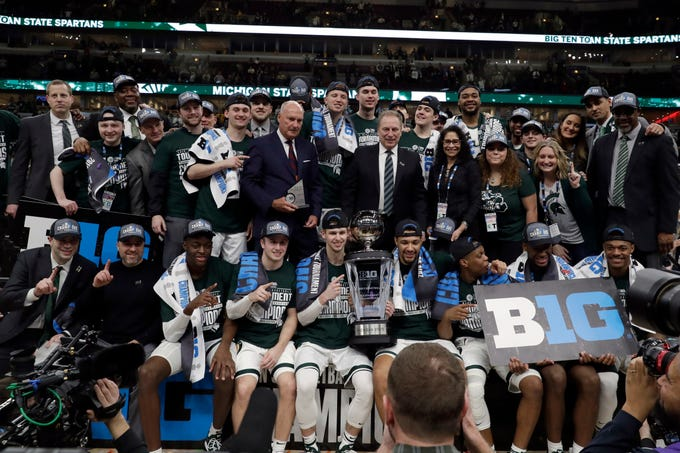 Michigan State players and coaches pose with the championship trophy after defeating Michigan 65-60 in an NCAA college basketball championship game in the Big Ten Conference tournament, Sunday, March 17, 2019, in Chicago.