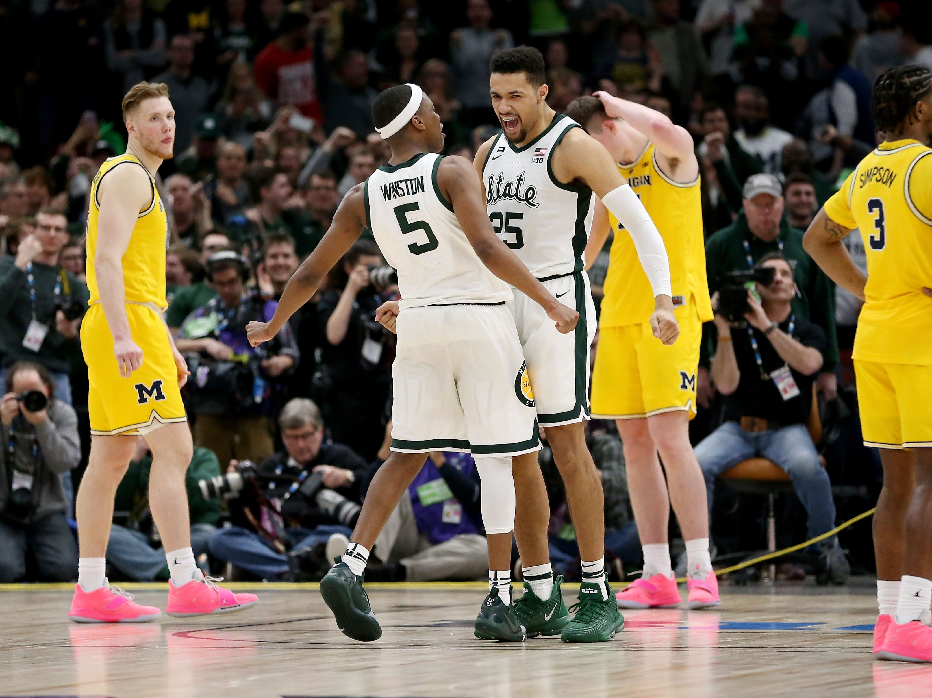 Cassius Winston #5 and Kenny Goins #25 of the Michigan State Spartans celebrate in the second half against the Michigan Wolverines during the championship game of the Big Ten Basketball Tournament at the United Center on March 17, 2019 in Chicago, Illinois.