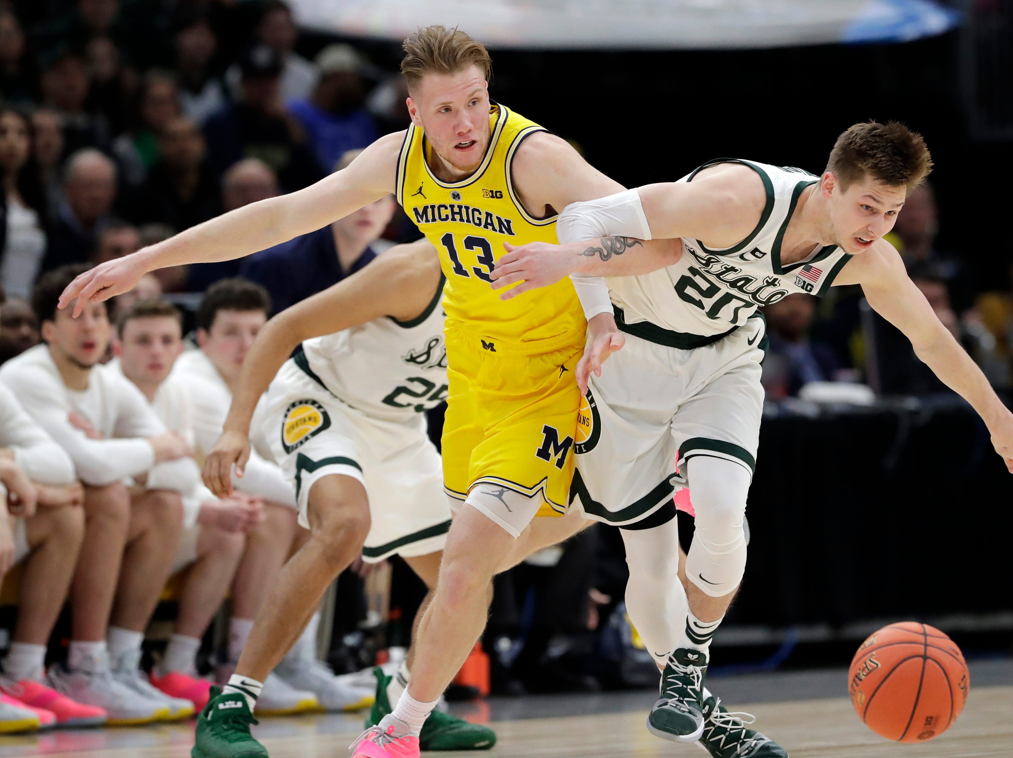 Michigan State's Matt McQuaid (20) and Michigan's Ignas Brazdeikis (13) battle for a loose ball during the first half of an NCAA college basketball championship game in the Big Ten Conference tournament, Sunday, March 17, 2019, in Chicago.