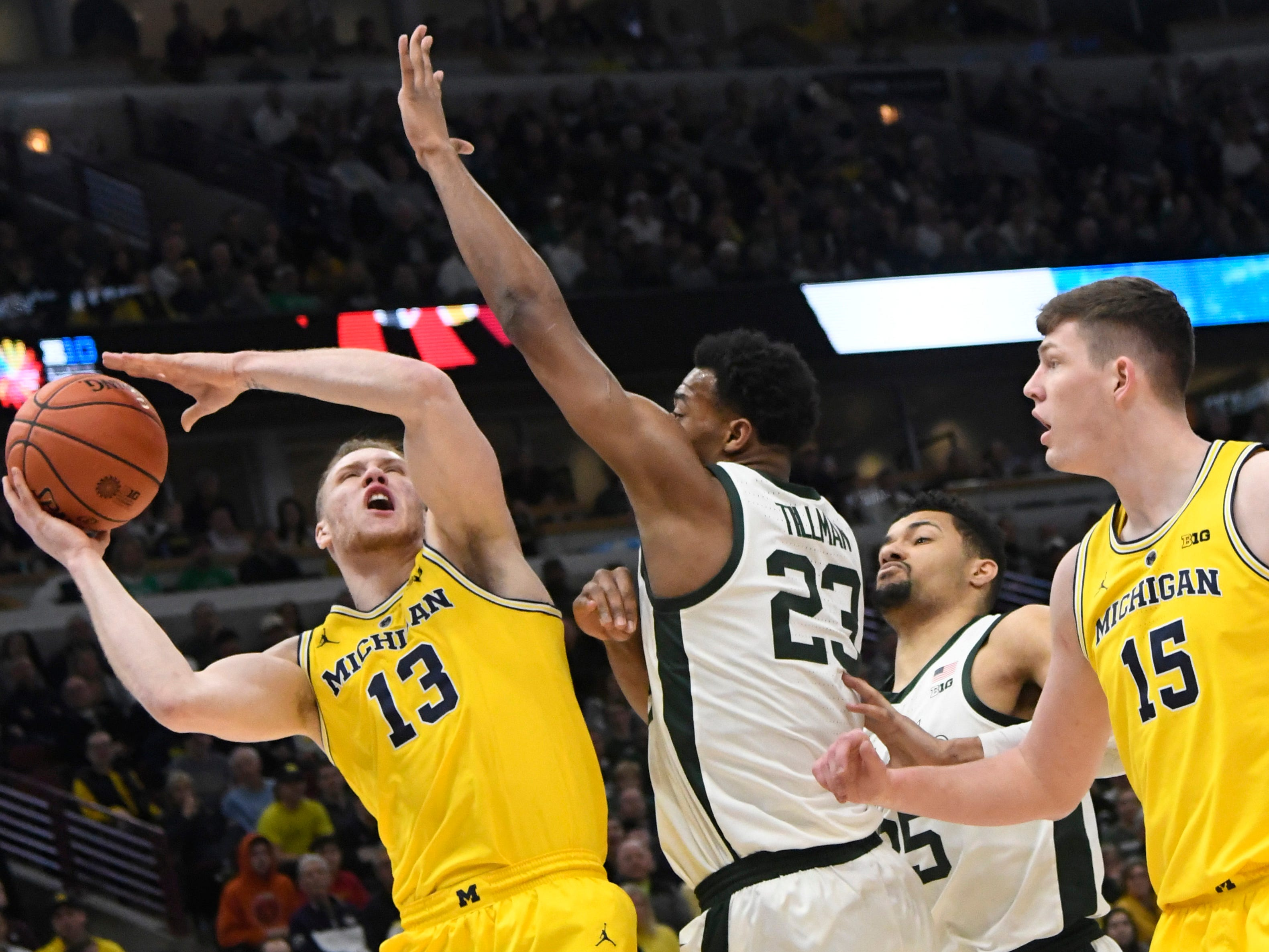 Michigan Wolverines forward Ignas Brazdeikis (13) Michigan State Spartans forward Xavier Tillman (23) during the first half in the Big Ten conference tournament at United Center.