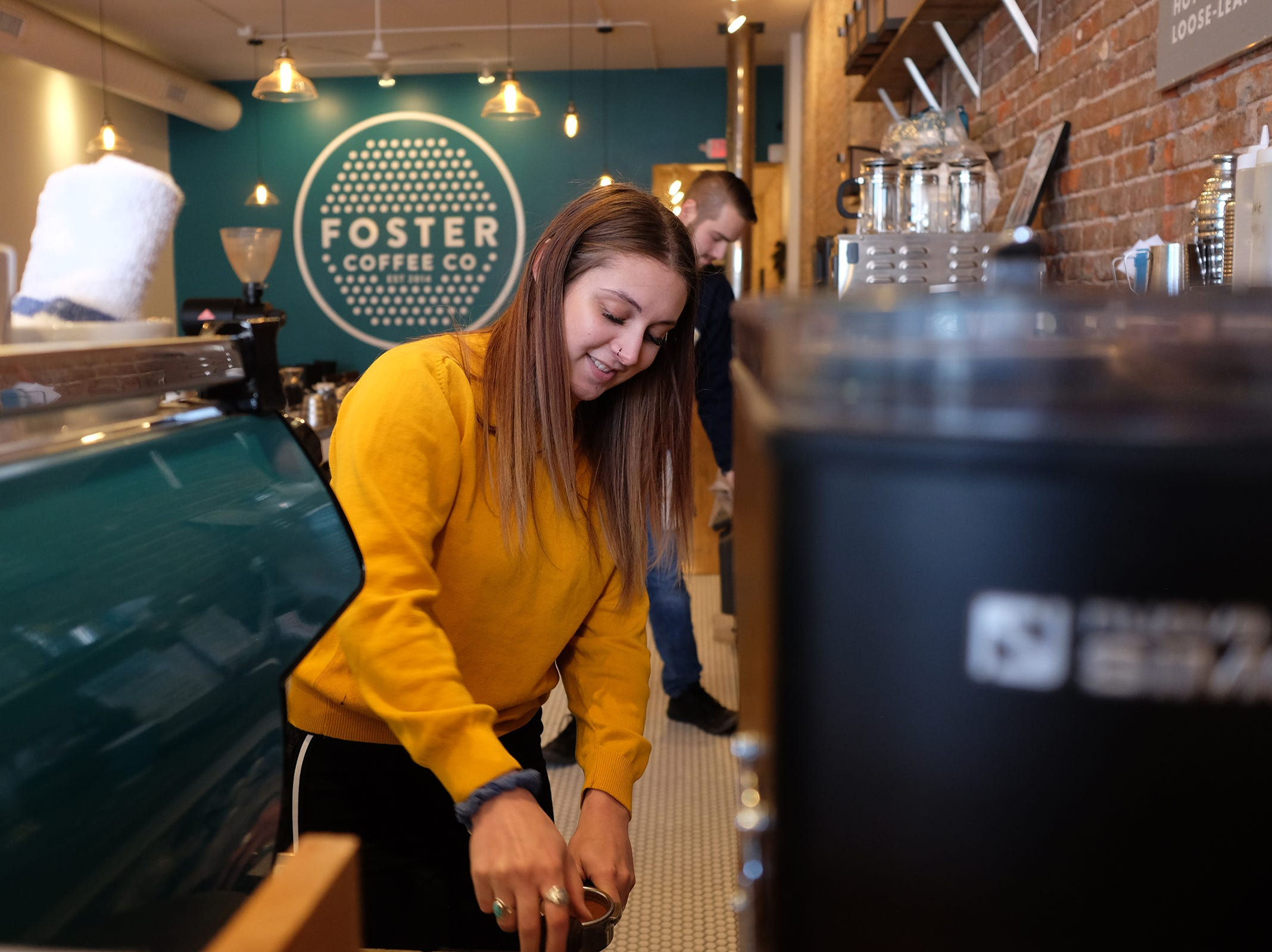 Barista Claire Munro at Foster Coffee Company in Owosso works on an order.