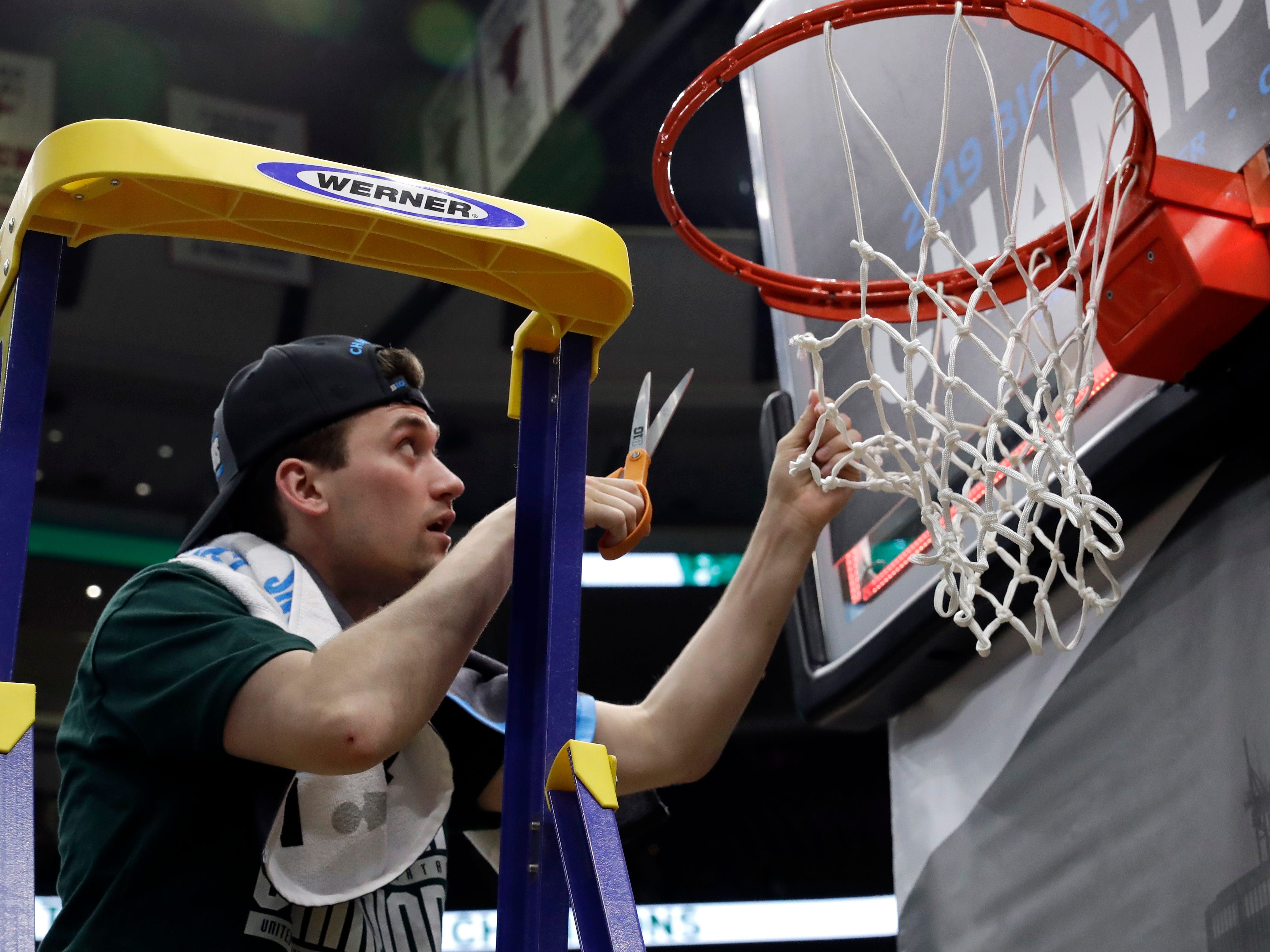 Michigan State's Foster Loyer cuts a piece of the net after defeating Michigan 65-60 in an NCAA college basketball championship game in the Big Ten Conference tournament, Sunday, March 17, 2019, in Chicago. (AP Photo/Nam Y. Huh)