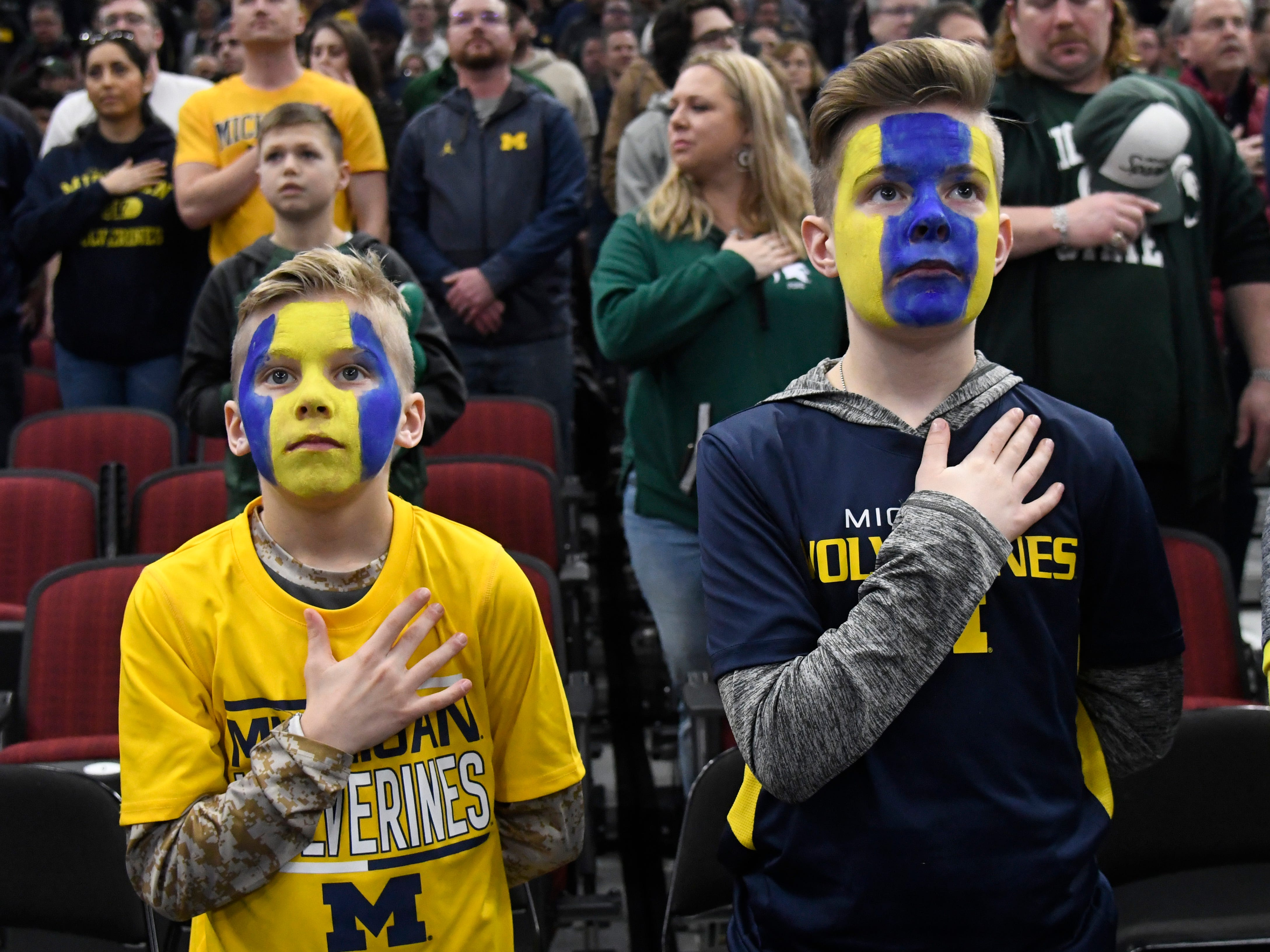 Michigan Wolverines fans stand for the national anthem before the game between the Michigan Wolverines and the Michigan State Spartans in the Big Ten conference tournament at United Center.