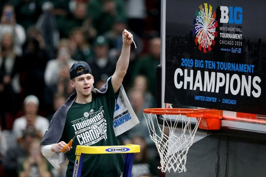 CHICAGO, ILLINOIS - MARCH 17:  Matt McQuaid #20 of the Michigan State Spartans cuts down the net after beating the Michigan Wolverines 65-60 in the championship game of the Big Ten Basketball Tournament at the United Center on March 17, 2019 in Chicago, Illinois. (Photo by Dylan Buell/Getty Images)