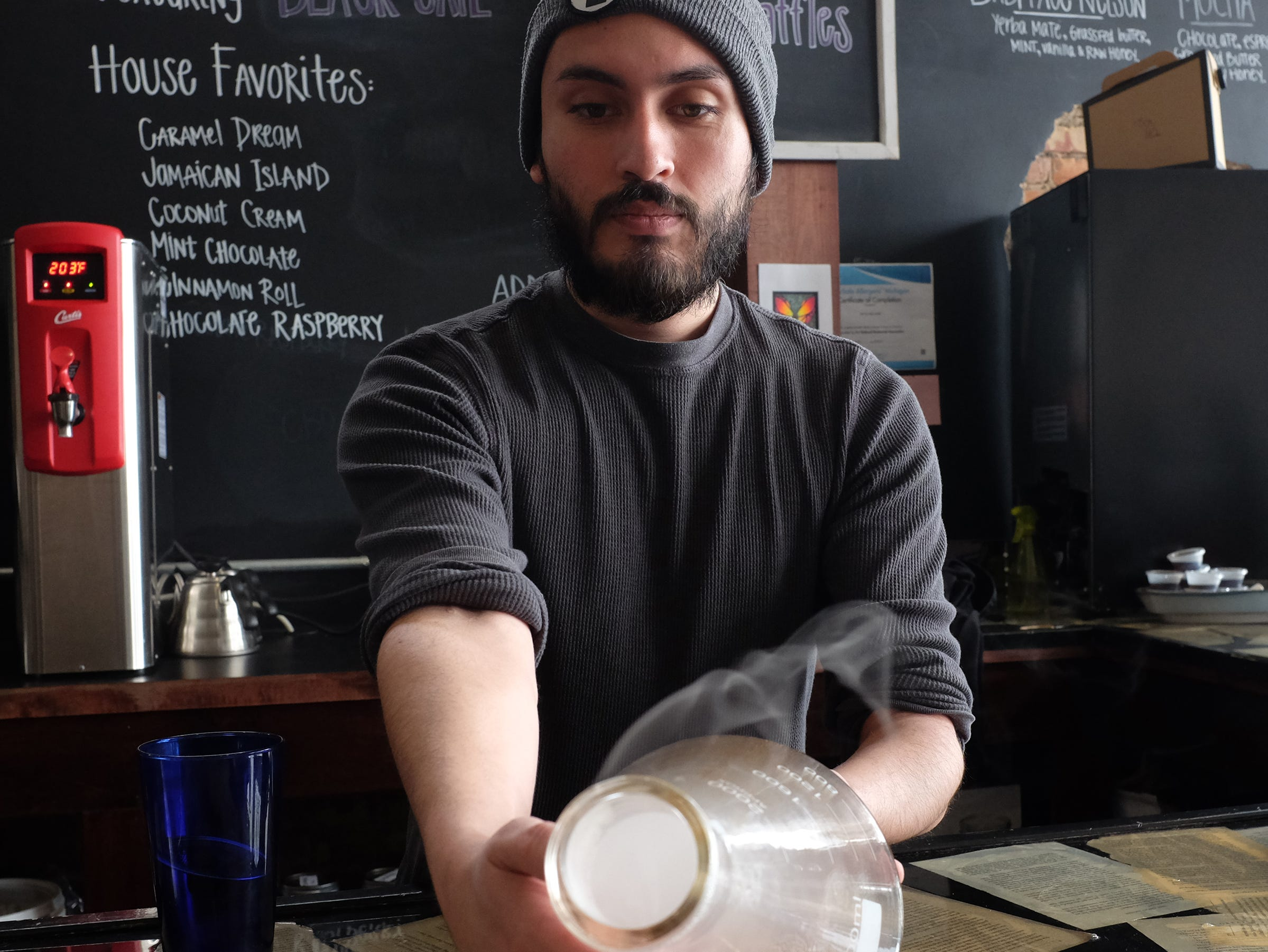 Barista Josh Martinez at The Crafted Bean in Lansing demonstrates a specialty drink called a Smoking Gun.