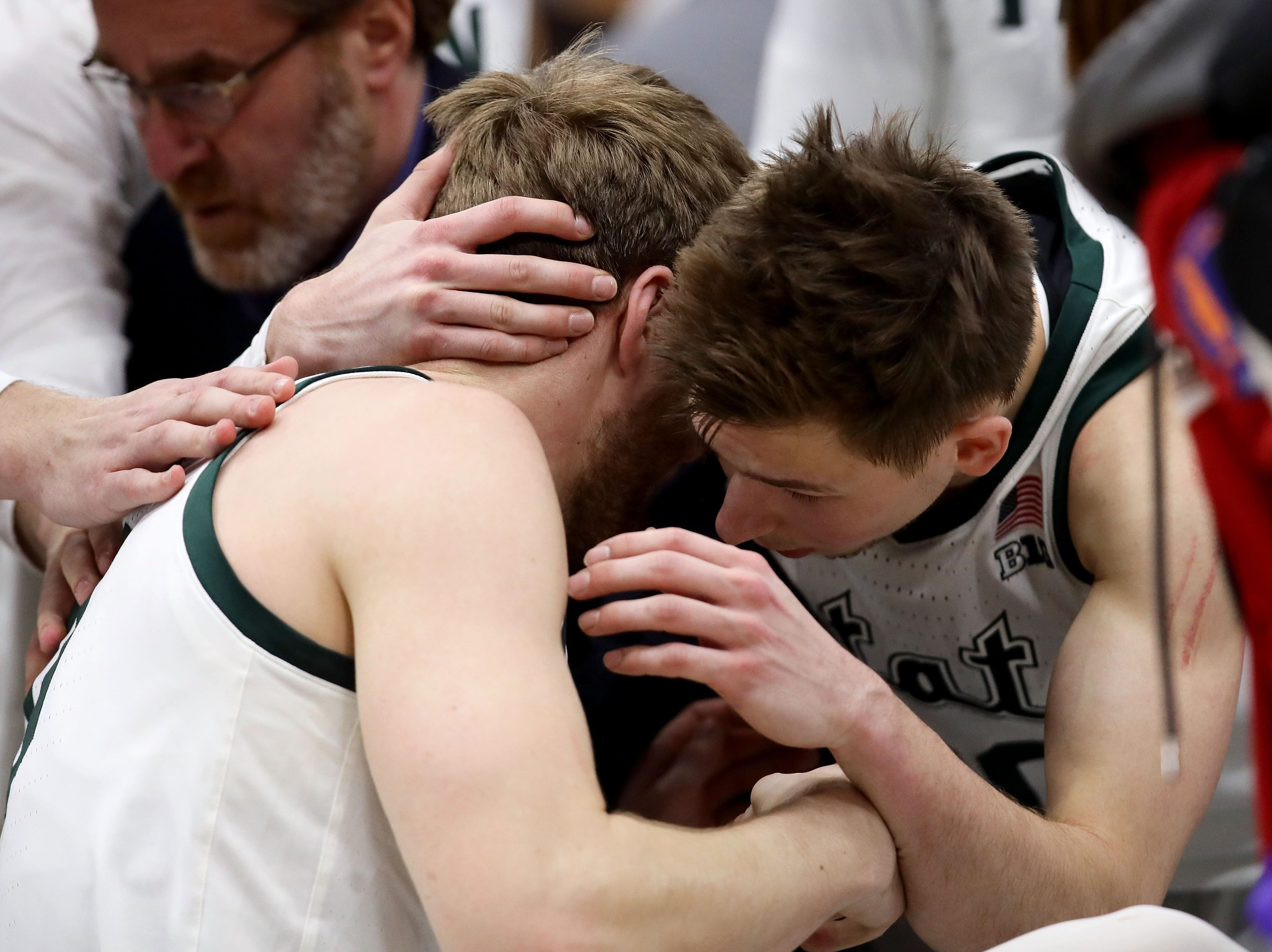 Kyle Ahrens #0 of the Michigan State Spartans #0 and Matt McQuaid #20 meet after Ahrens was injured in the first half against the Michigan Wolverines during the championship game of the Big Ten Basketball Tournament at the United Center on March 17, 2019 in Chicago, Illinois.