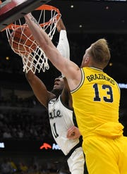Michigan State Spartans forward Aaron Henry (11)  dunks the ball as Michigan Wolverines forward Ignas Brazdeikis (13) defends him during the second half in the Big Ten conference tournament at United Center.