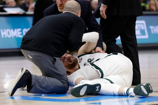 Medical personnel checks on Michigan State's Kyle Ahrens during the first half of an NCAA college basketball championship game against Michigan in the Big Ten Conference tournament, Sunday, March 17, 2019, in Chicago.