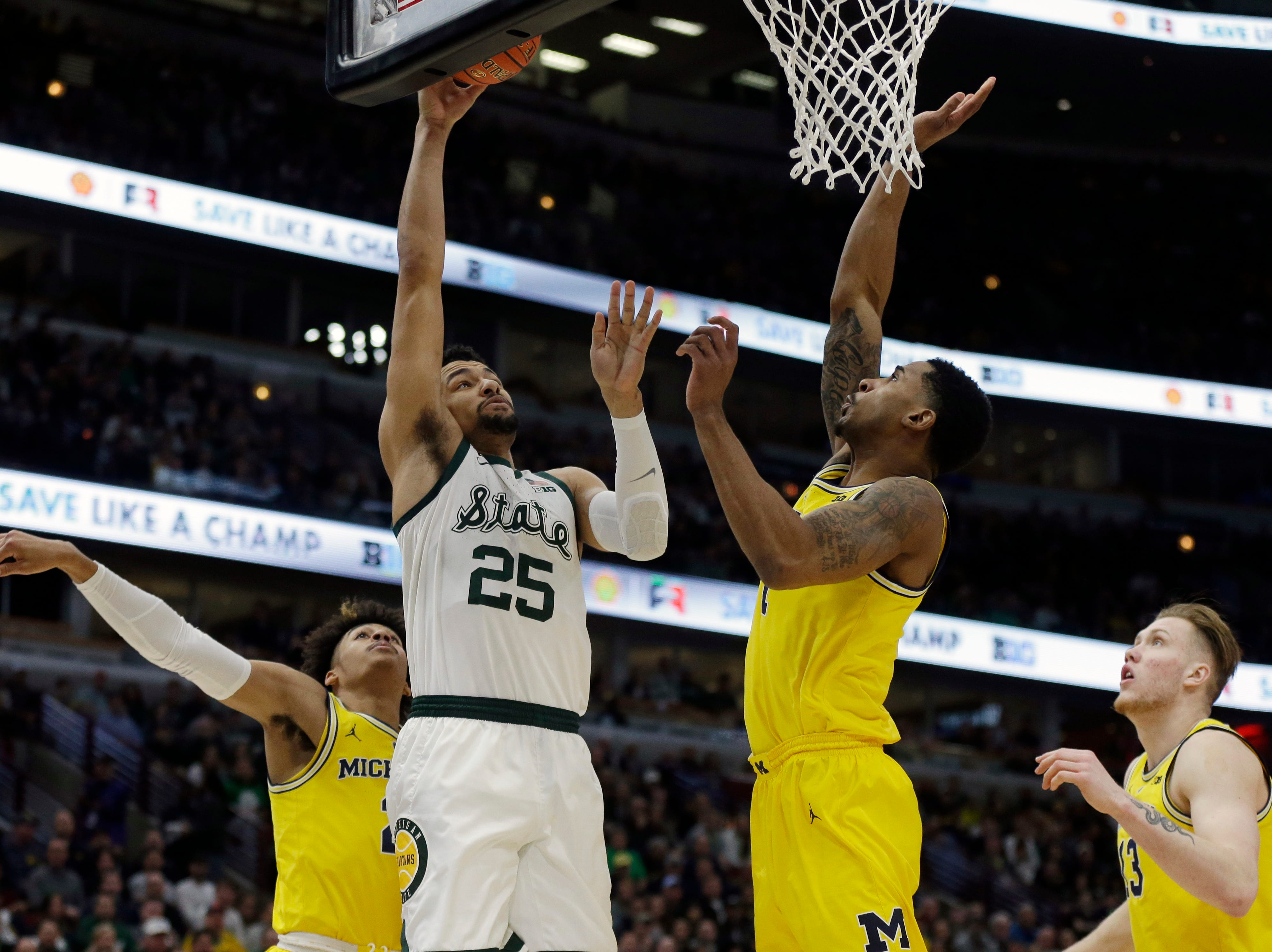 Michigan State's Kenny Goins (25) goes up for a basket against Michigan's Charles Matthews (1) during the first half of an NCAA college basketball championship game in the Big Ten Conference tournament, Sunday, March 17, 2019, in Chicago.