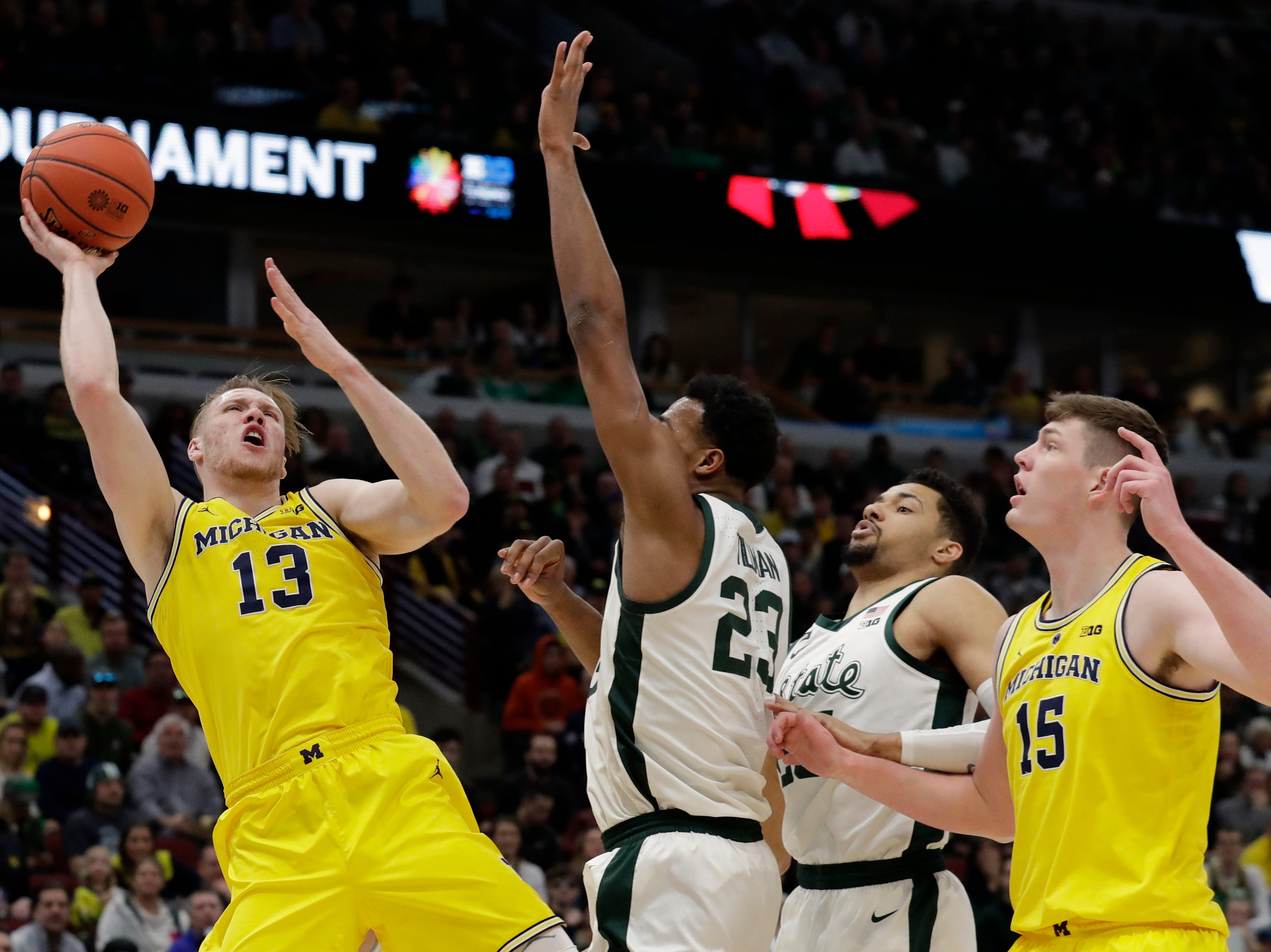 Michigan's Ignas Brazdeikis (13) goes up for a shot against Michigan State's Xavier Tillman (23) during the first half of an NCAA college basketball championship game in the Big Ten Conference tournament, Sunday, March 17, 2019, in Chicago.