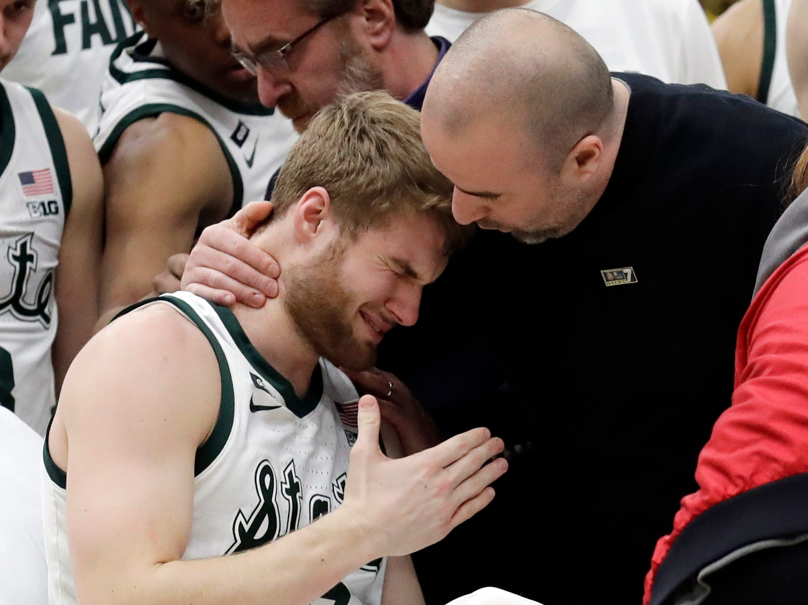 A medical personnel took talks to Michigan State's Kyle Ahrens, left, as Ahrens was the taken out of the court for injury during the first half of an NCAA college basketball championship game against Michigan in the Big Ten Conference tournament, Sunday, March 17, 2019, in Chicago.