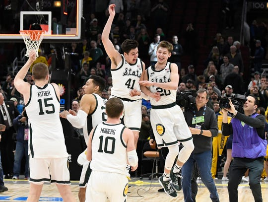 Connor George (41) and Matt McQuaid (20) celebrate MSU's Big Ten tournament win over Michigan last Sunday.