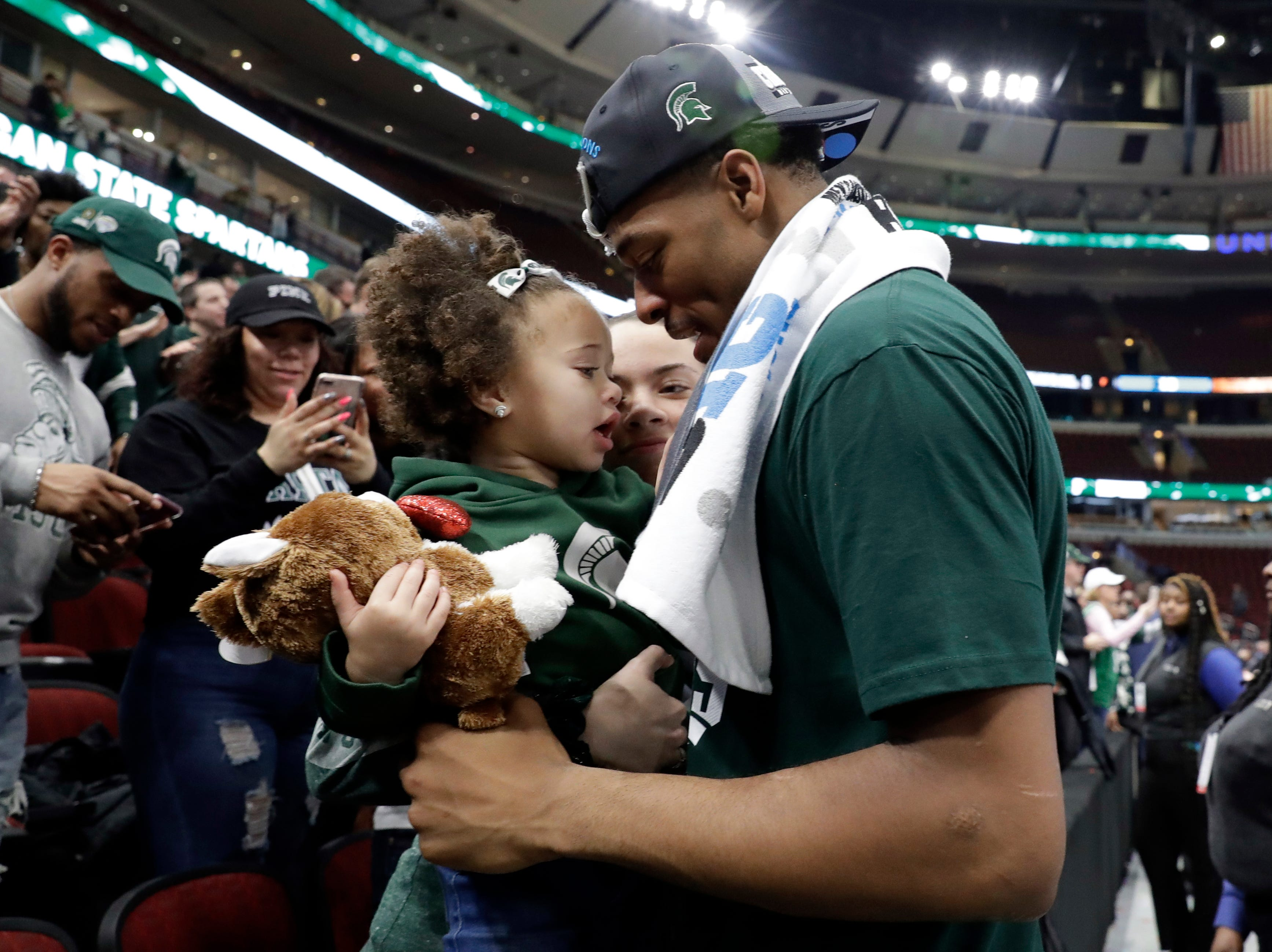 Michigan State's Xavier Tillman celebrates with his daughter after defeating Michigan 65-60 in an NCAA college basketball championship game in the Big Ten Conference tournament, Sunday, March 17, 2019, in Chicago. (AP Photo/Nam Y. Huh)