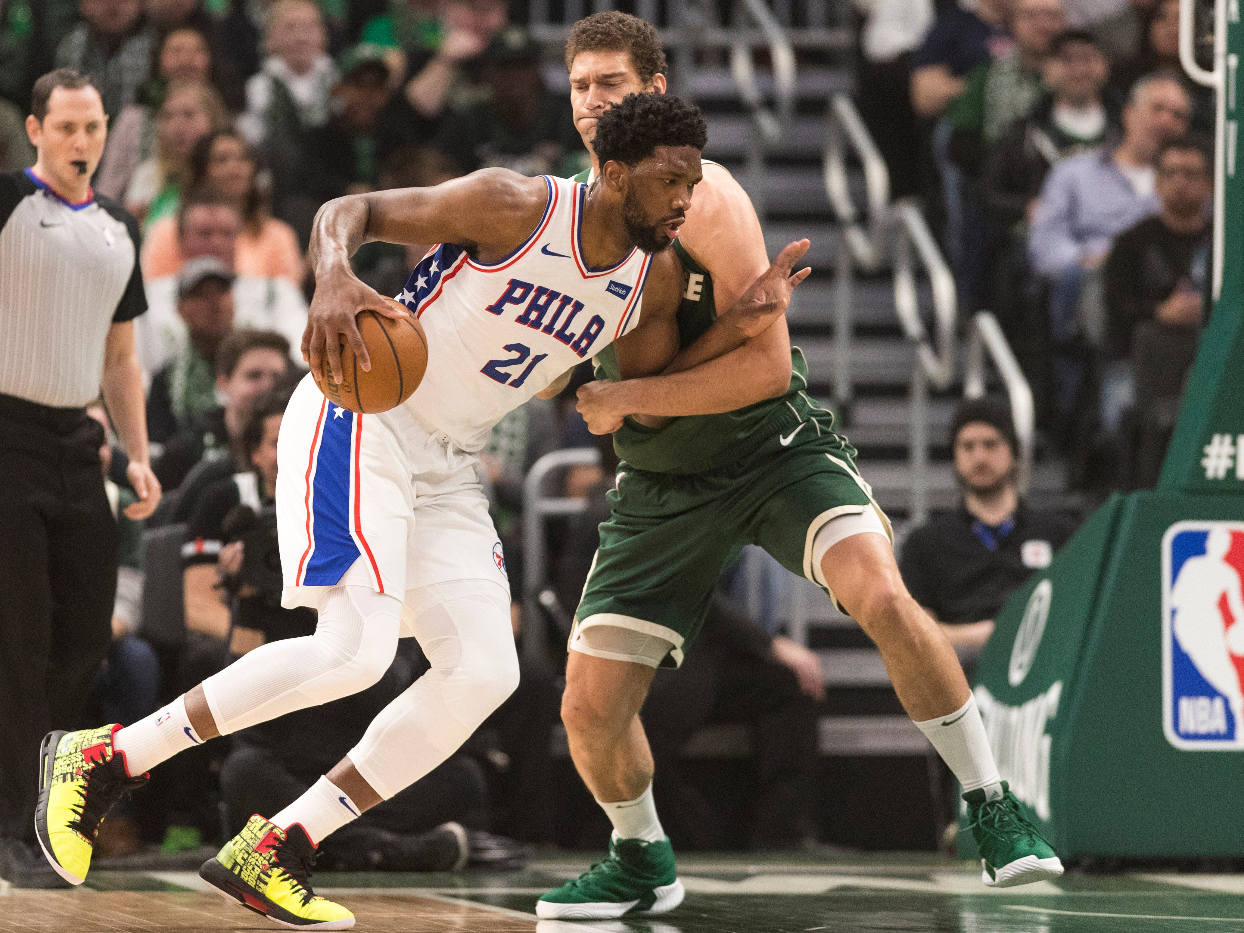76ers center Joel Embiid works against Bucks center Brook Lopez just outside the paint during the first quarter.
