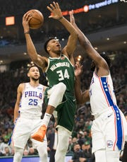 Bucks forward Giannis Antetokounmpo goes up to score two of his career-high 52 points over 76ers center Joel Embiid in their previous meeting March 17.