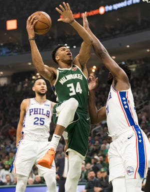 Bucks forward Giannis Antetokounmpo goes up to score two of his career-high 52 points over 76ers center Joel Embiid during the first quarter.