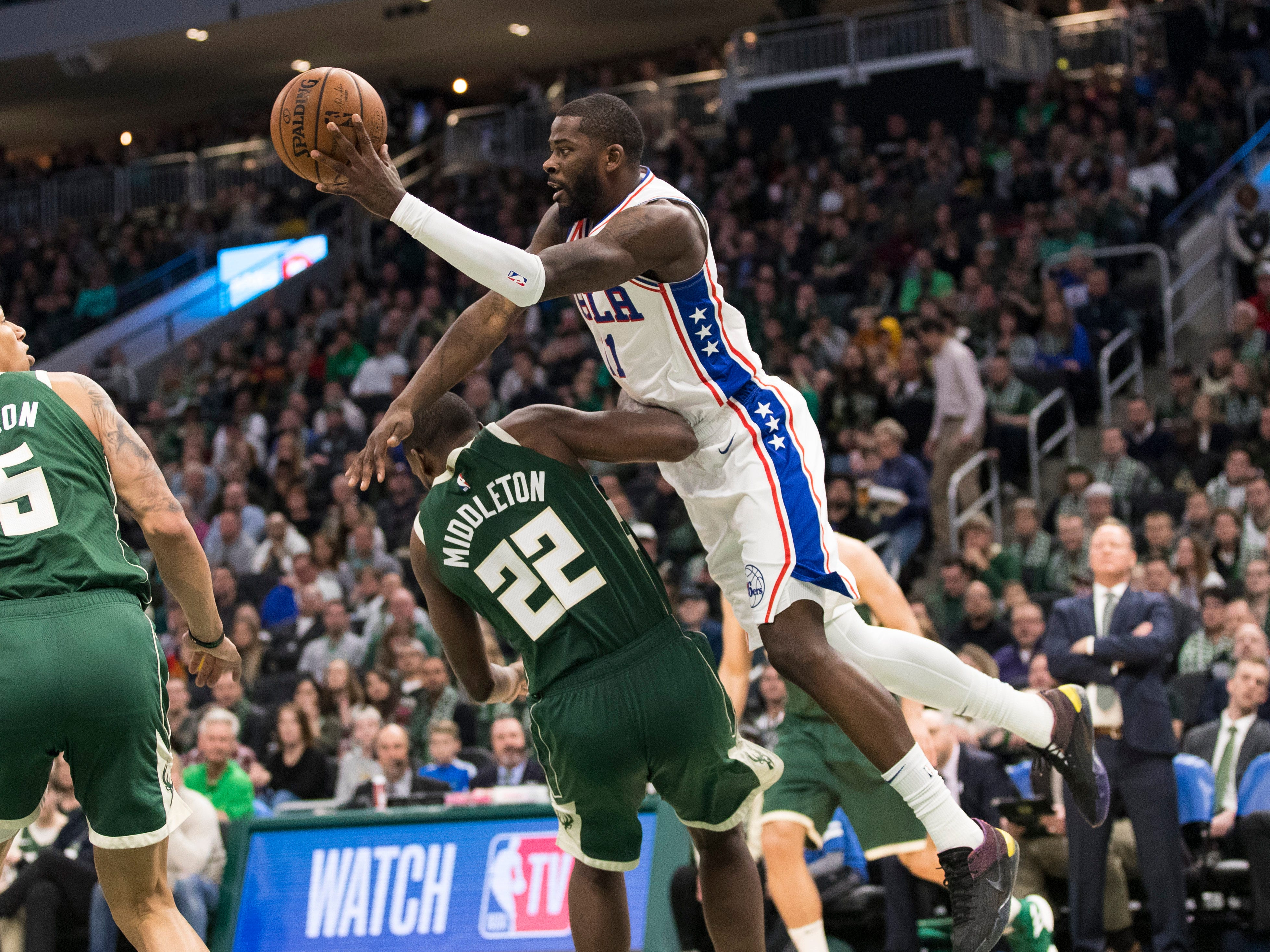 Bucks forward Khris Middleton draws an offense foul on James Ennis III of the Sixers during the fourth quarter.