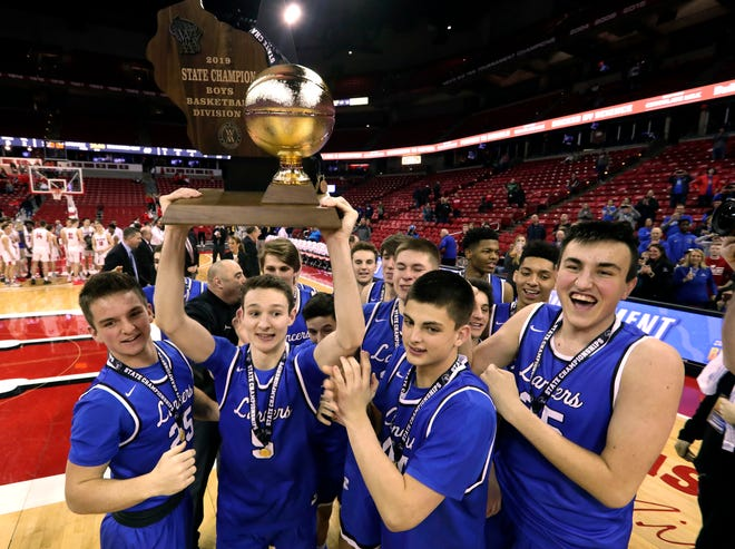 Brookfield Central players hoist the Division 1 trophy after their 69-52 win over Sun Prairie's in the 2019 title game.