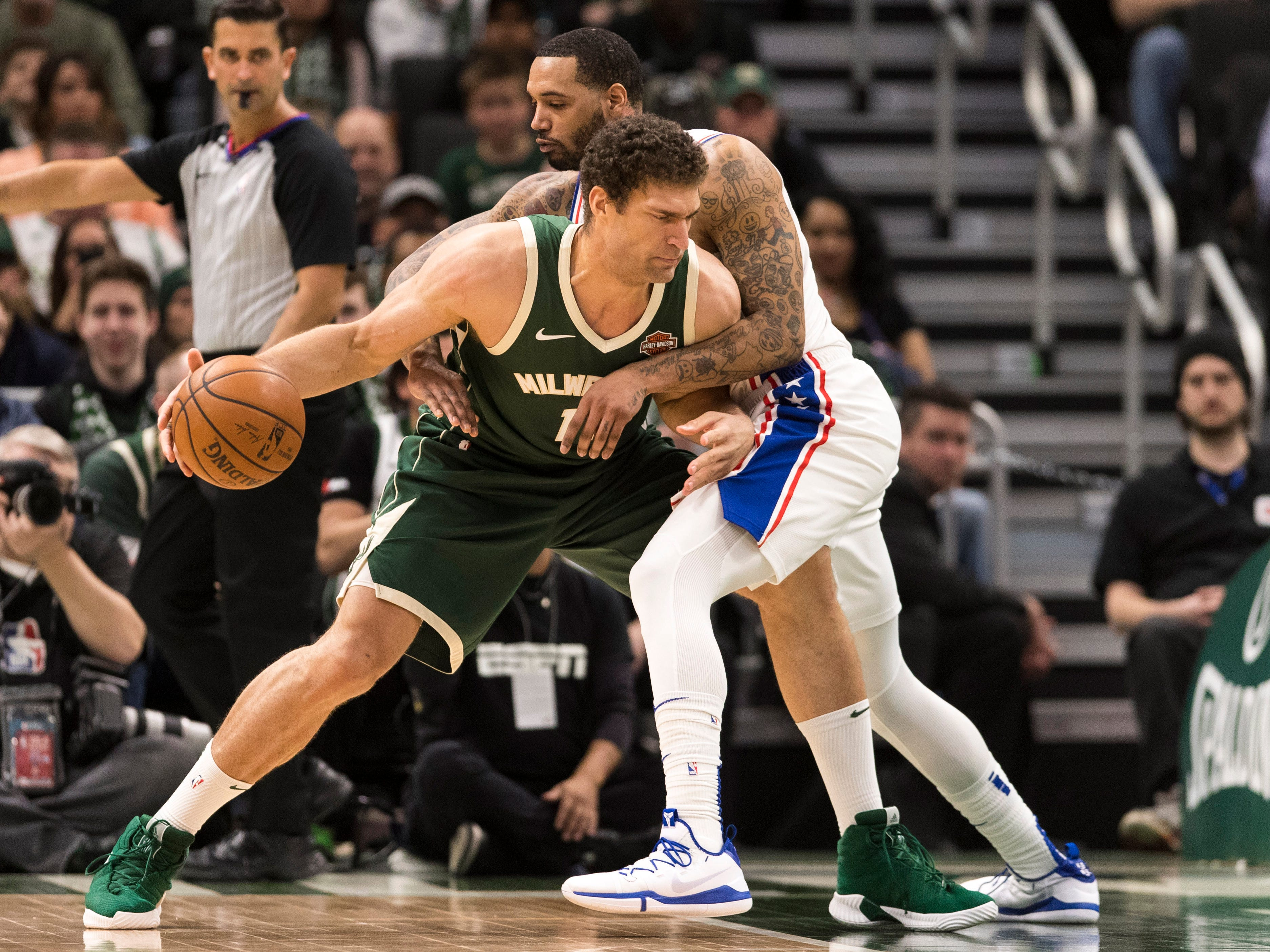Bucks center Brook Lopez just about gets a hug from Mike Scott as he tries to back down the 76ers forward during the fourth quarter.