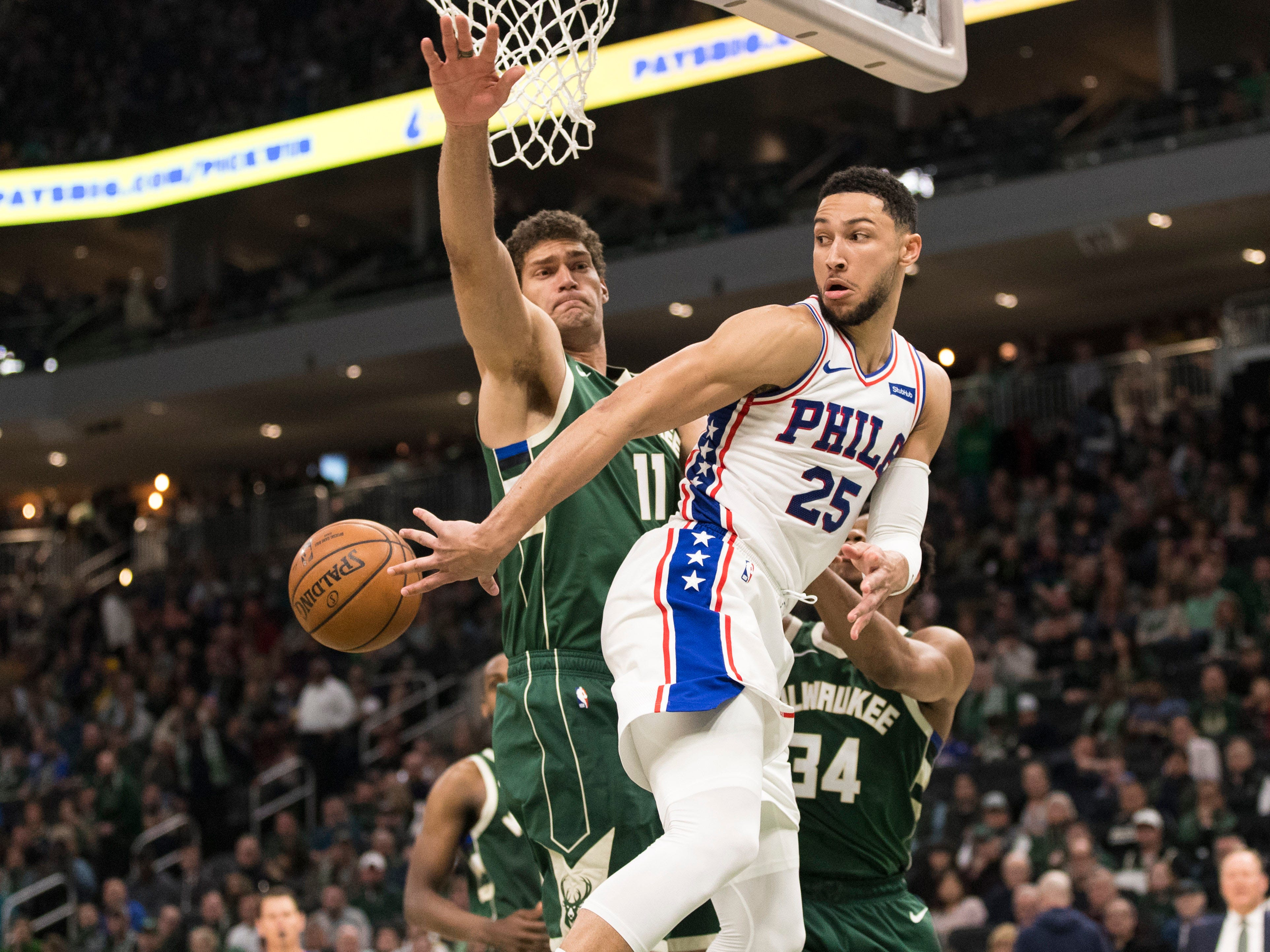 76ers guard Ben Simmons throws a backward pass after being confronted by Bucks center Brook Lopez underneath the basket during the third quarter.