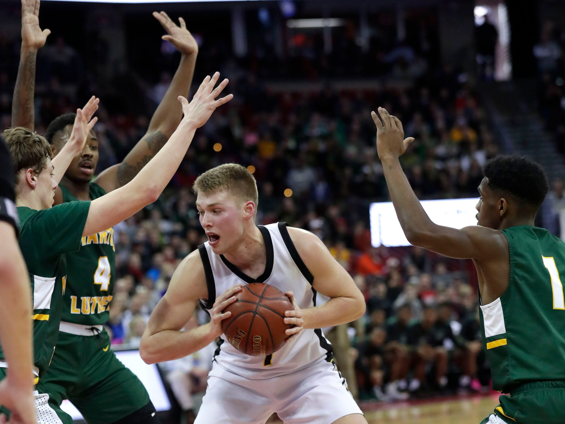 Waupun senior Marcus Domask is surrounded by a trio of Martin Luther defenders Saturday.