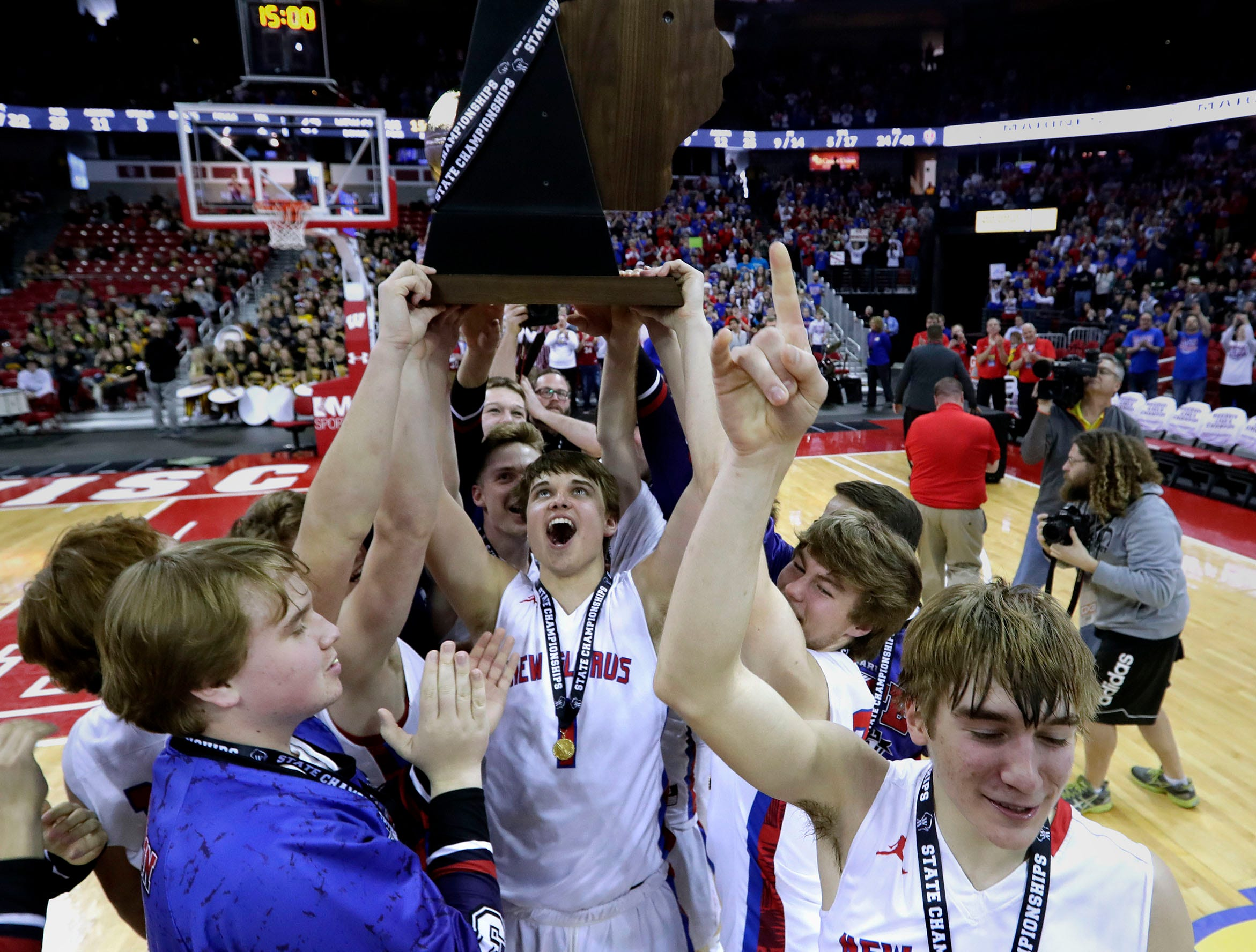 New Glarus players show off their WIAA Division 4 championship trophy after beating Oshkosh Lourdes, 67-62, in the title game Saturday.