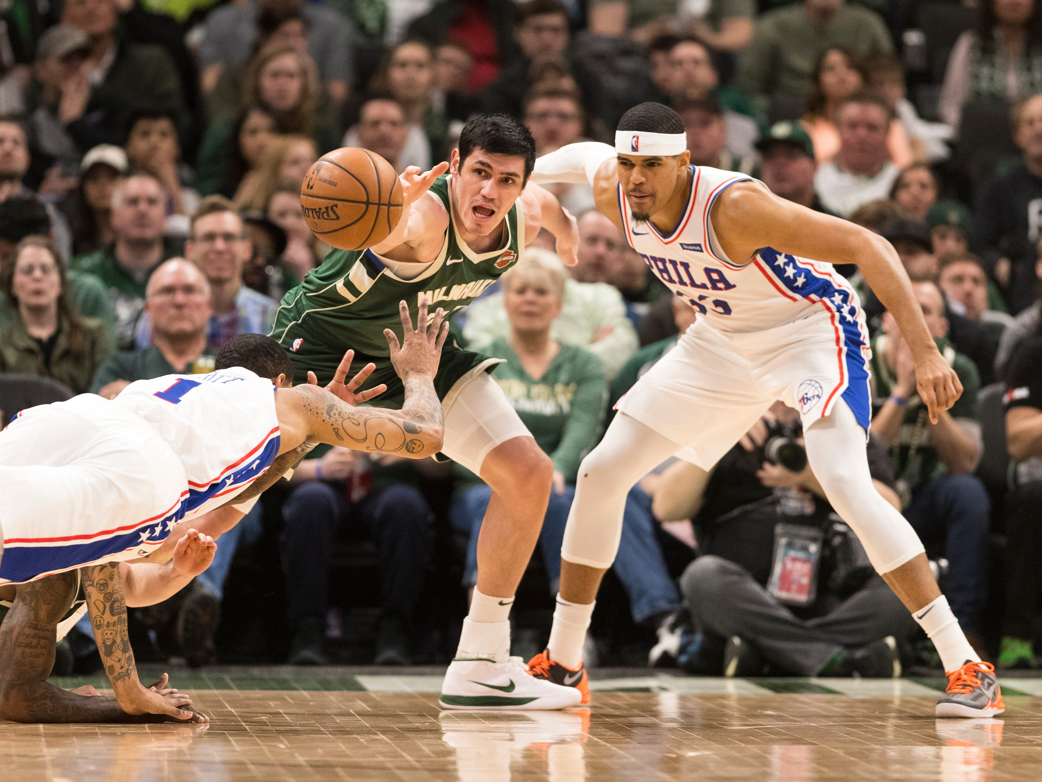 Players from both teams hit the deck as Bucks forward Ersan Ilyasova moves in to grab a loose ball Sunday.