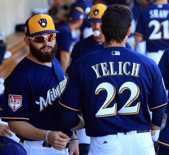 Good friends Baker Mayfield and Christian Yelich talk in the Brewers dugout during the team's game against Colorado on Saturday.