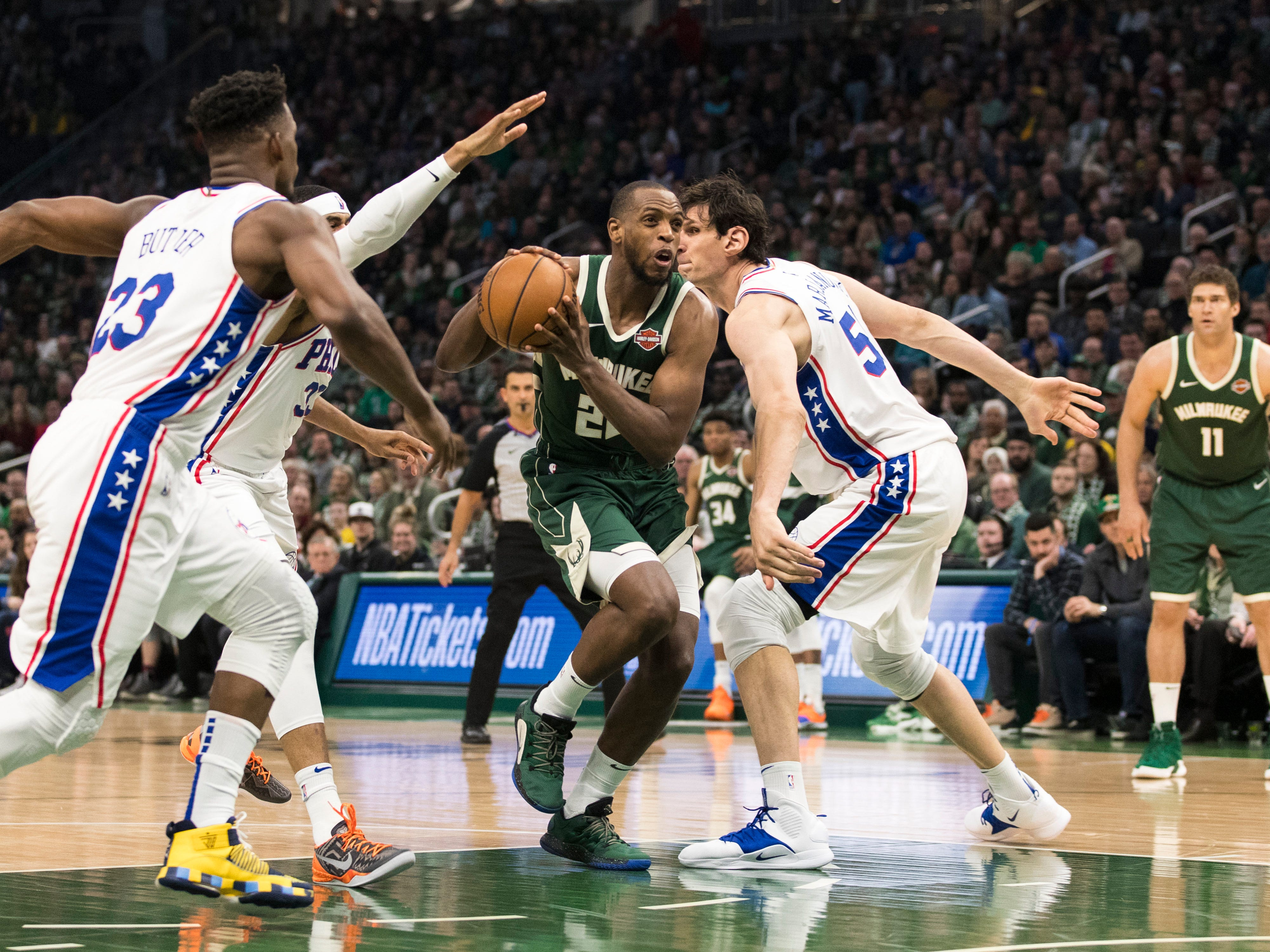Bucks forward Khris Middleton knifes through a trio of Sixers defenders and down the lane during the second quarter.
