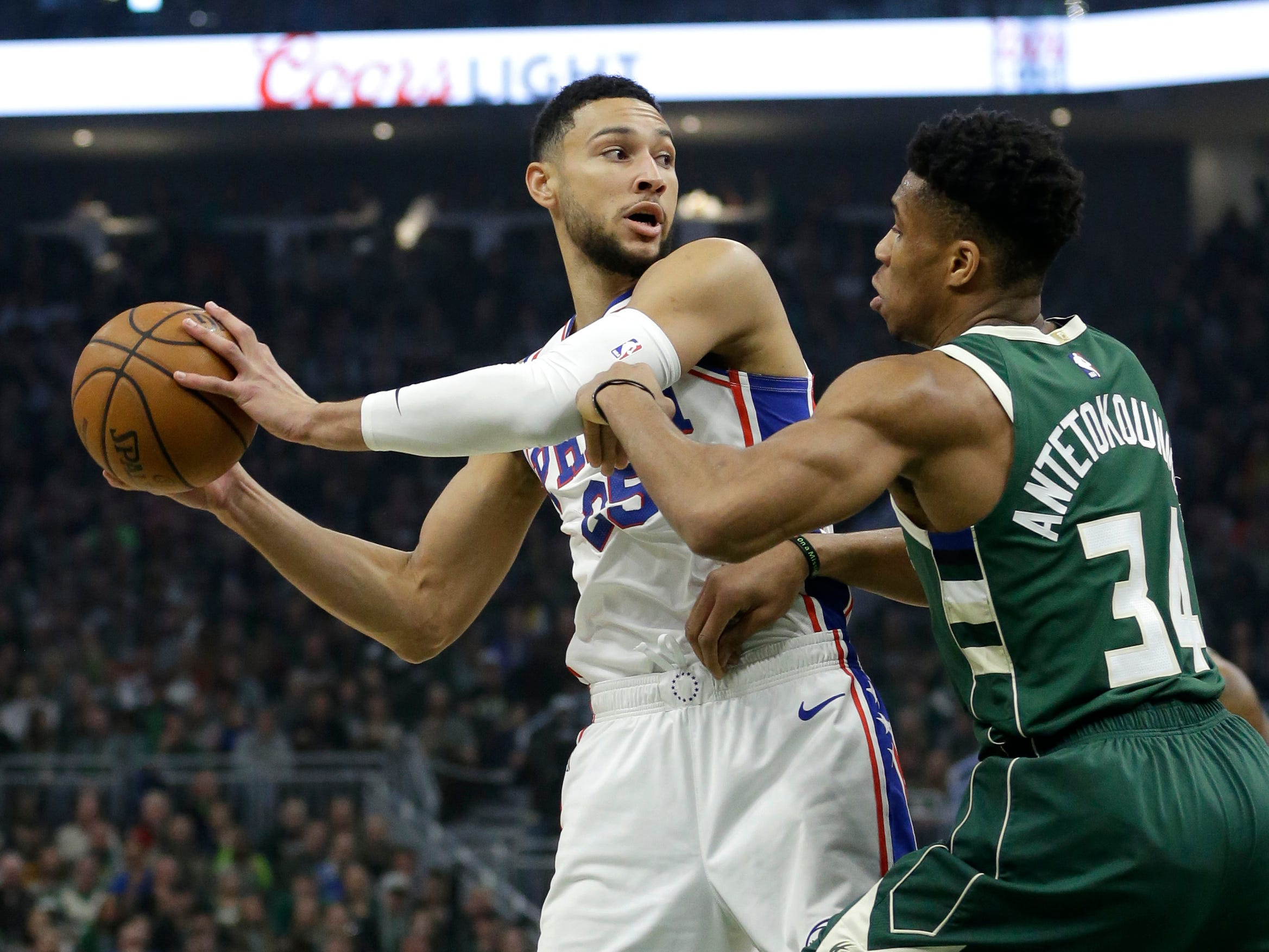 76ers guard Ben Simmons looks for a teammate to pass to while being guarded by Giannis Antetokounmpo of the Bucks during the first half Sunday.