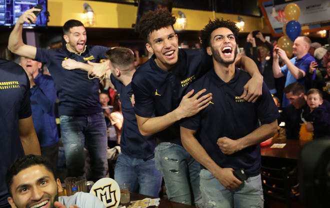 Marquette's Markus Howard (far right) and teammate, Brendan Bailey, celebrate after learning the team earned a No. 5 seed in the West regional of the NCAA Tournament and will play 12th-seeded Murray State on Thursdayin Hartford, Conn..