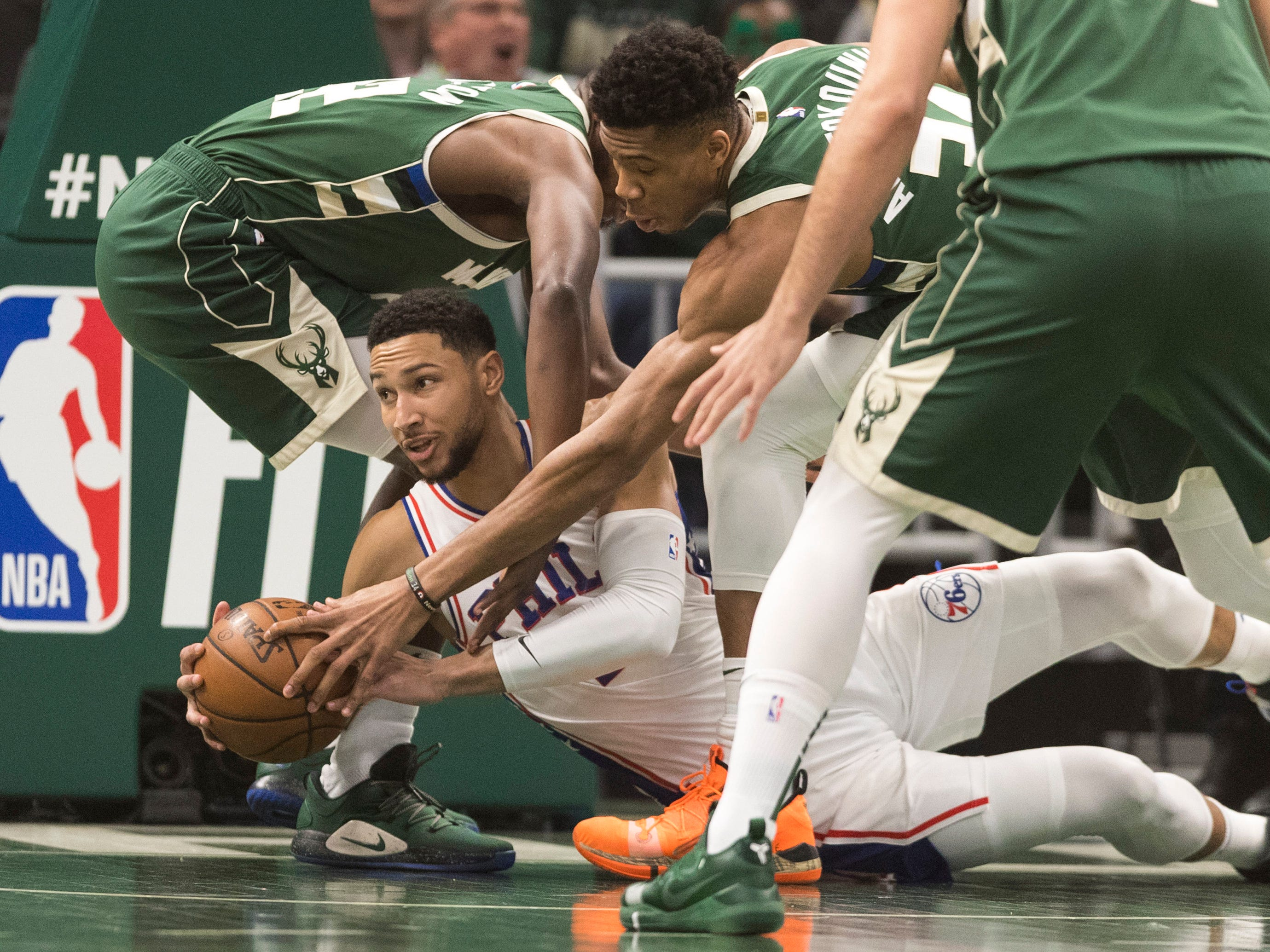 76ers guard Ben Simmons attempts to get the ball to an open teammate before Giannis Antetokounmpo can pry it from his hands during the first quarter.