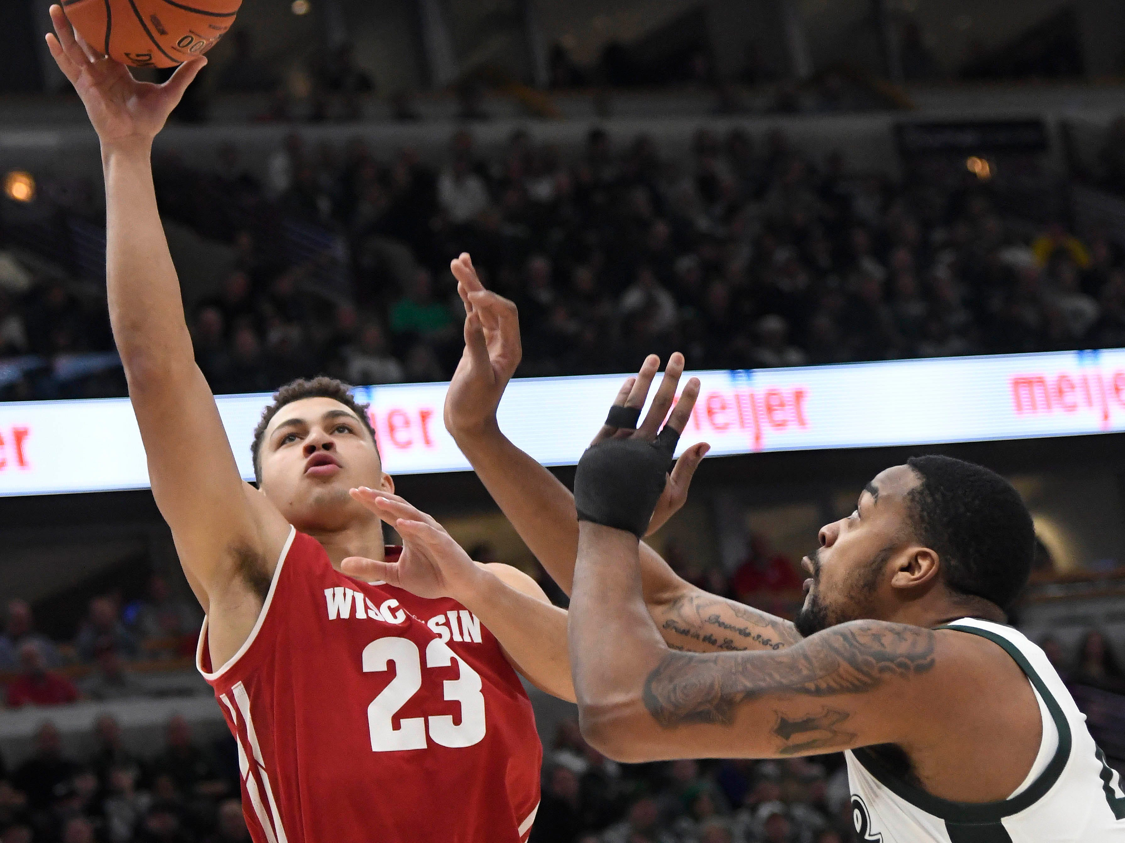 Kobe King of the Badgers goes up for a shot near the basket against Michigan State forward Nick Ward during the first half.