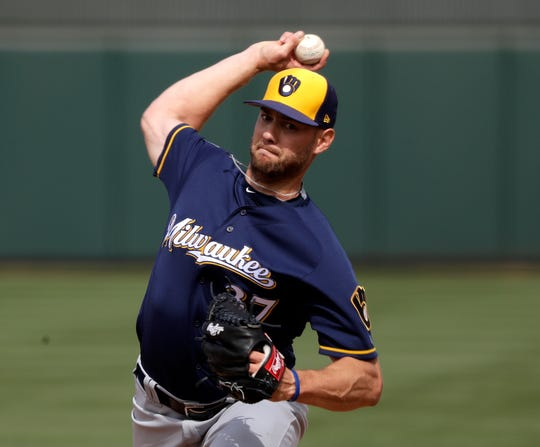 Brewers relief pitcher Adrian Houser throws against the Athletics in a spring training game March 9.