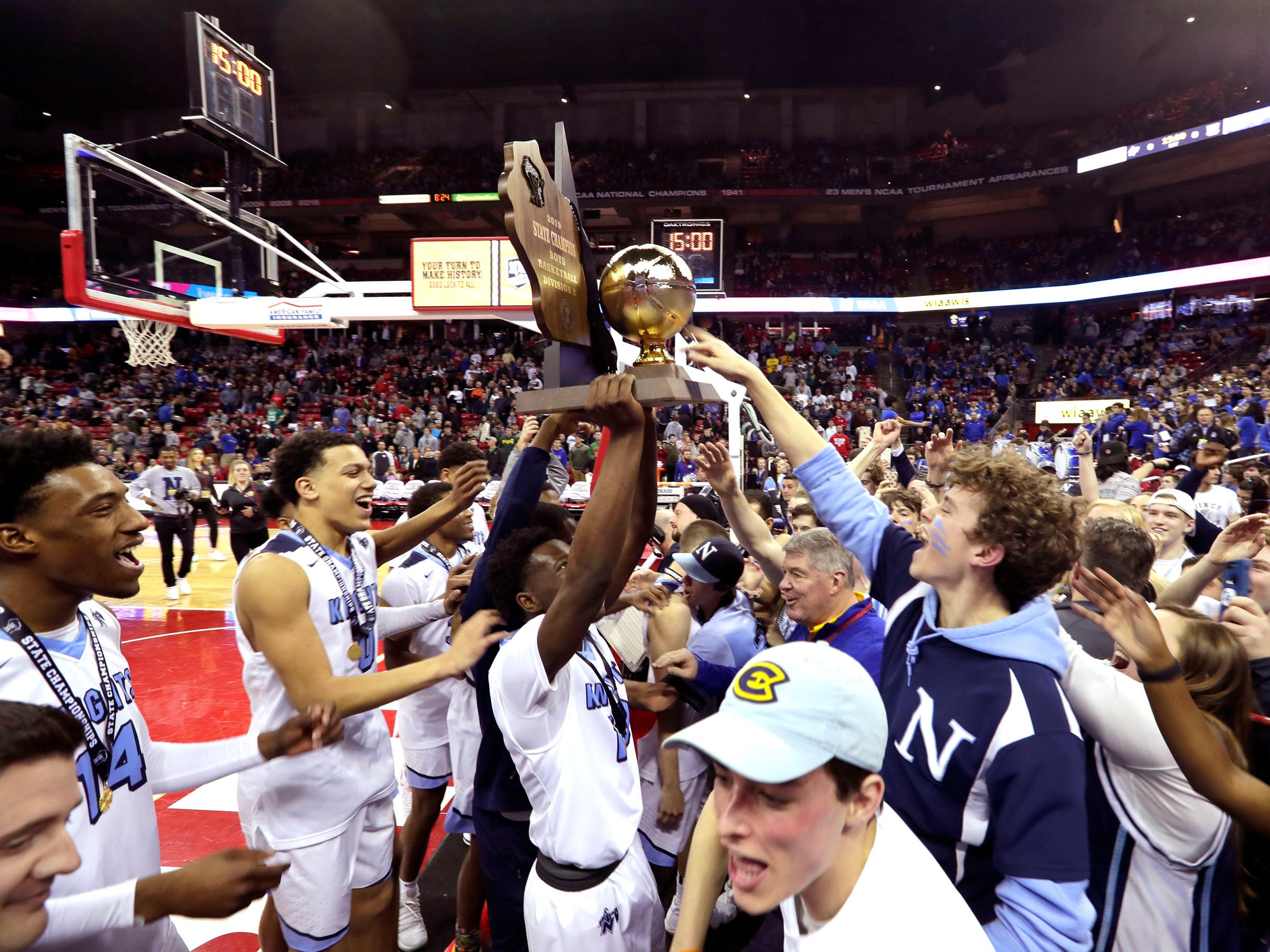 Nicolet players show off their Division 2 championship trophy to their fellow classmates Saturday.