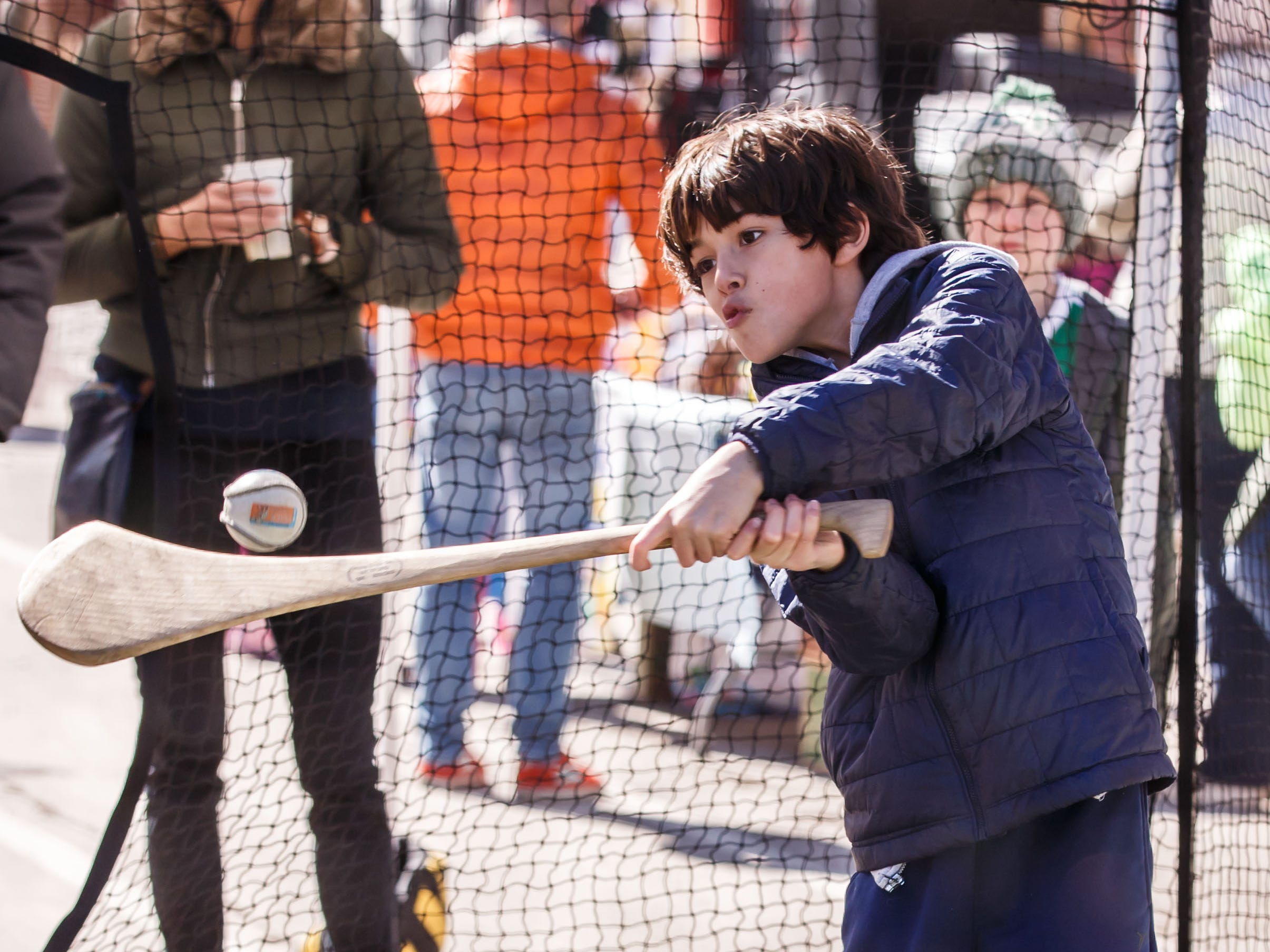 Quinn Bailey, 9, of Shorewood tries the game of Hurling at the Milwaukee Hurling Club booth during the Shorewood Shenanigans street festival on Saturday, March 16, 2019. The annual event features live music, food and drink, games, vendors and more. Nine bars and restaurants along N. Oakland Ave. participate in the fun.