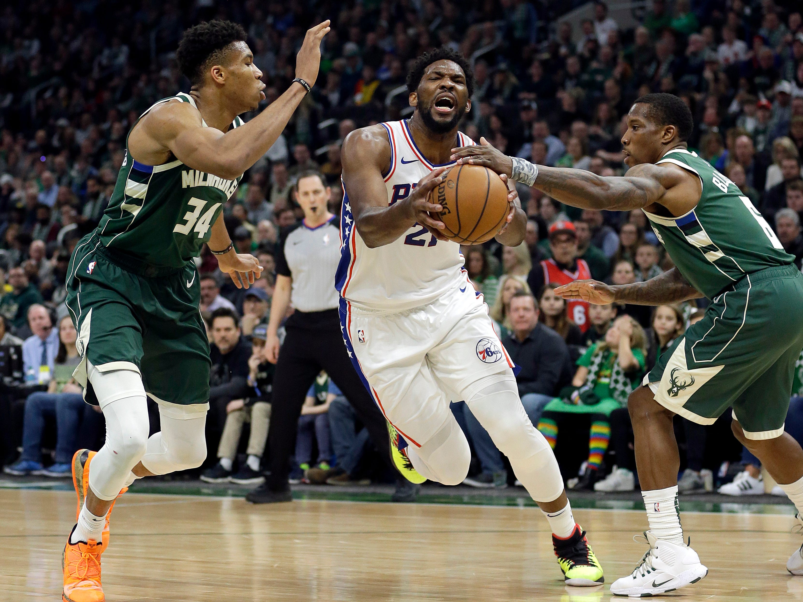 Sixer center Philadelphia 76ers' Joel Embiid drives between the Bucks' Giannis Antetokounmpo and Eric Bledsoe during the first half.