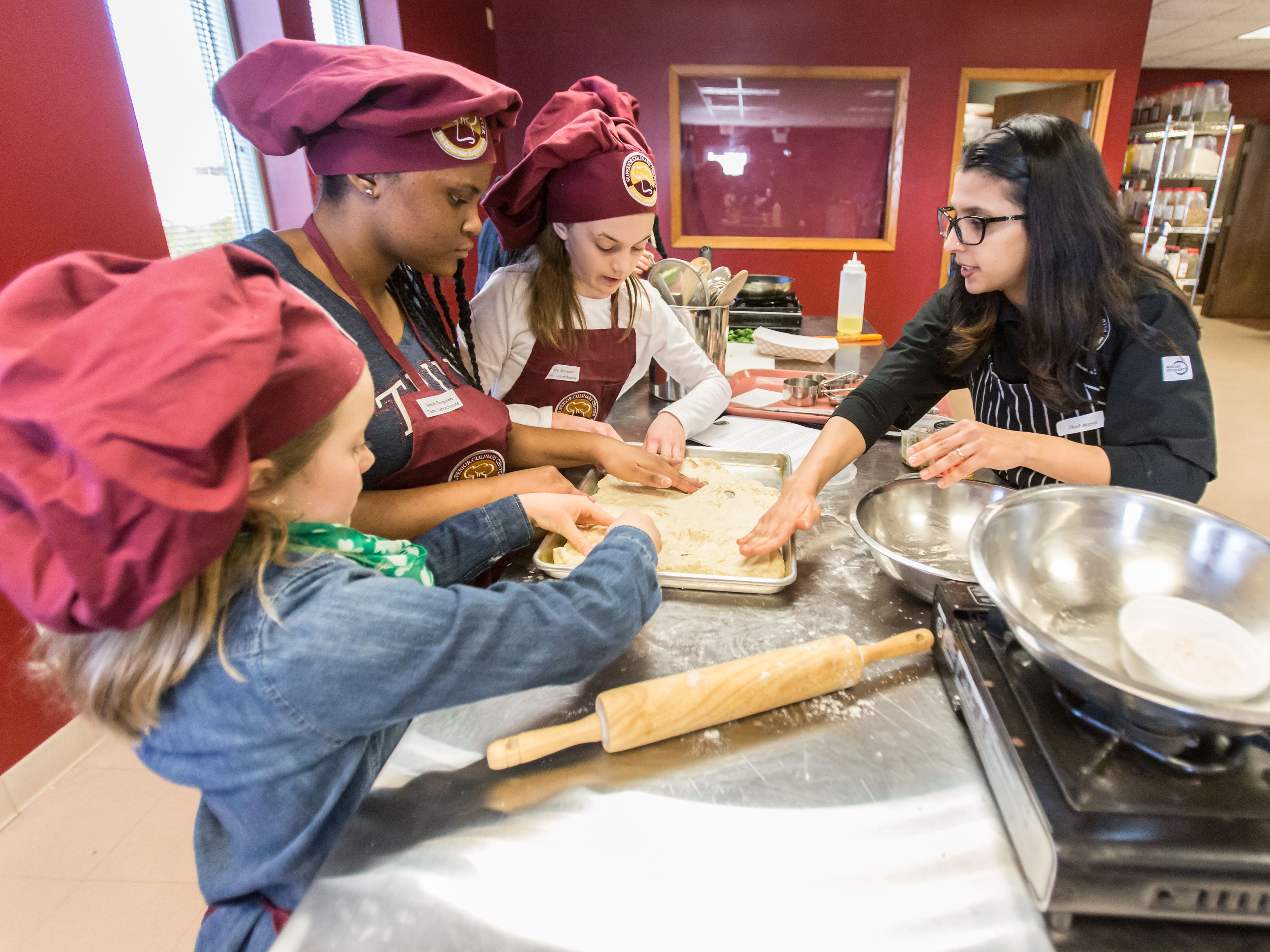 Chef Maria Khan (right) helps (from left) Kendall Johnson, 9, of Port Washington, Saniah Ferguson, 13, of Milwaukee and Avery Johnson, 11, of Port Washington, prepare a homemade green pizza during the St. Patrick's Kids Cooking Class at Superior Culinary Center in Saint Francis on Saturday, March 16, 2019. During the class youngsters learned how to prepare green pizza, Irish brown soda bread, guacamole and chips, mint chocolate chip cake and a vanilla mint milkshake.