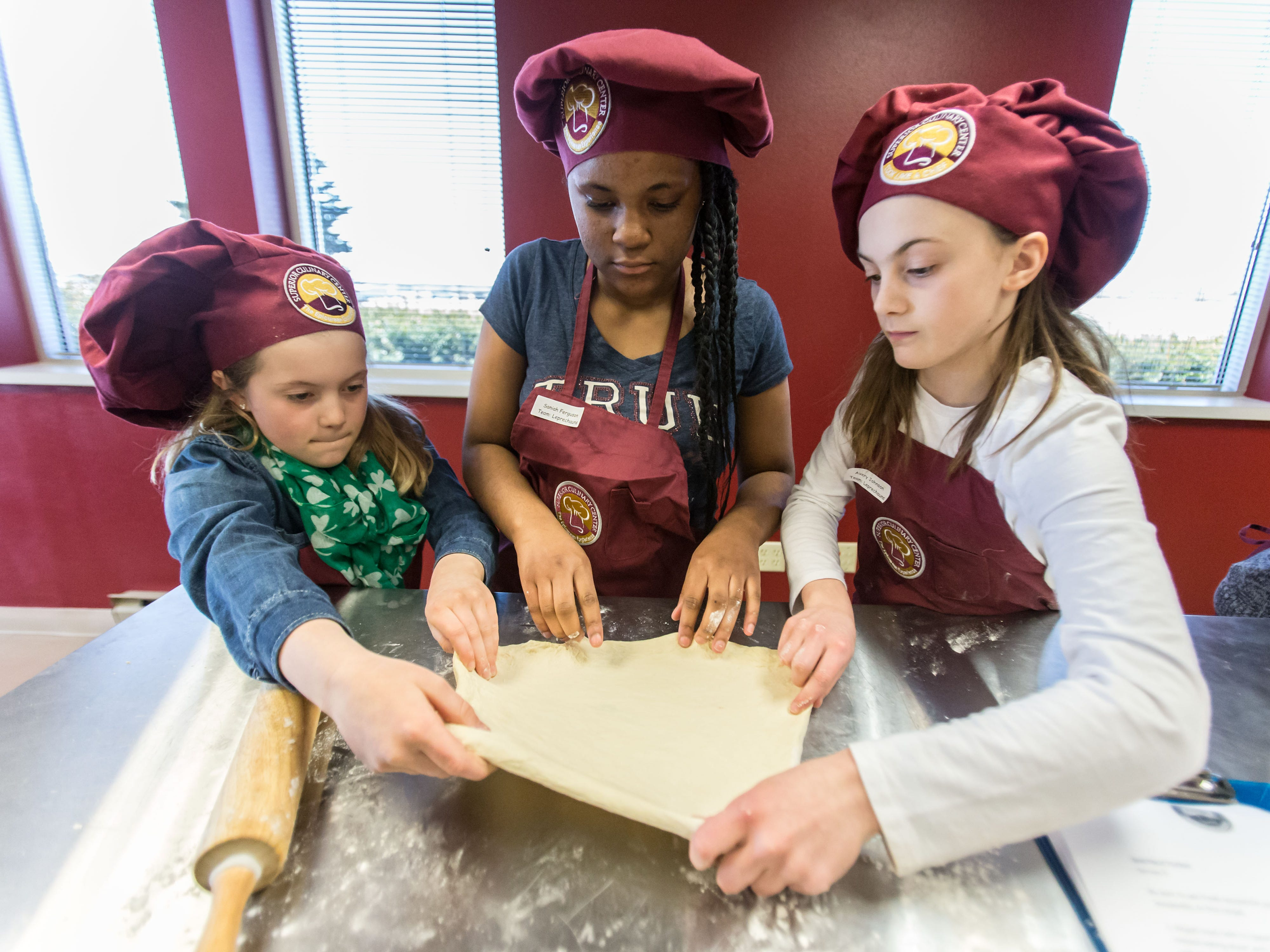 Chefs in training (from left) Kendall Johnson, 9, of Port Washington, Saniah Ferguson, 13, of Milwaukee and Avery Johnson, 11, of Port Washington, prepare dough for a homemade green pizza during the St. Patrick's Kids Cooking Class at Superior Culinary Center in Saint Francis on Saturday, March 16, 2019. Visit superiorculinarycenter.com for info on upcoming classes.