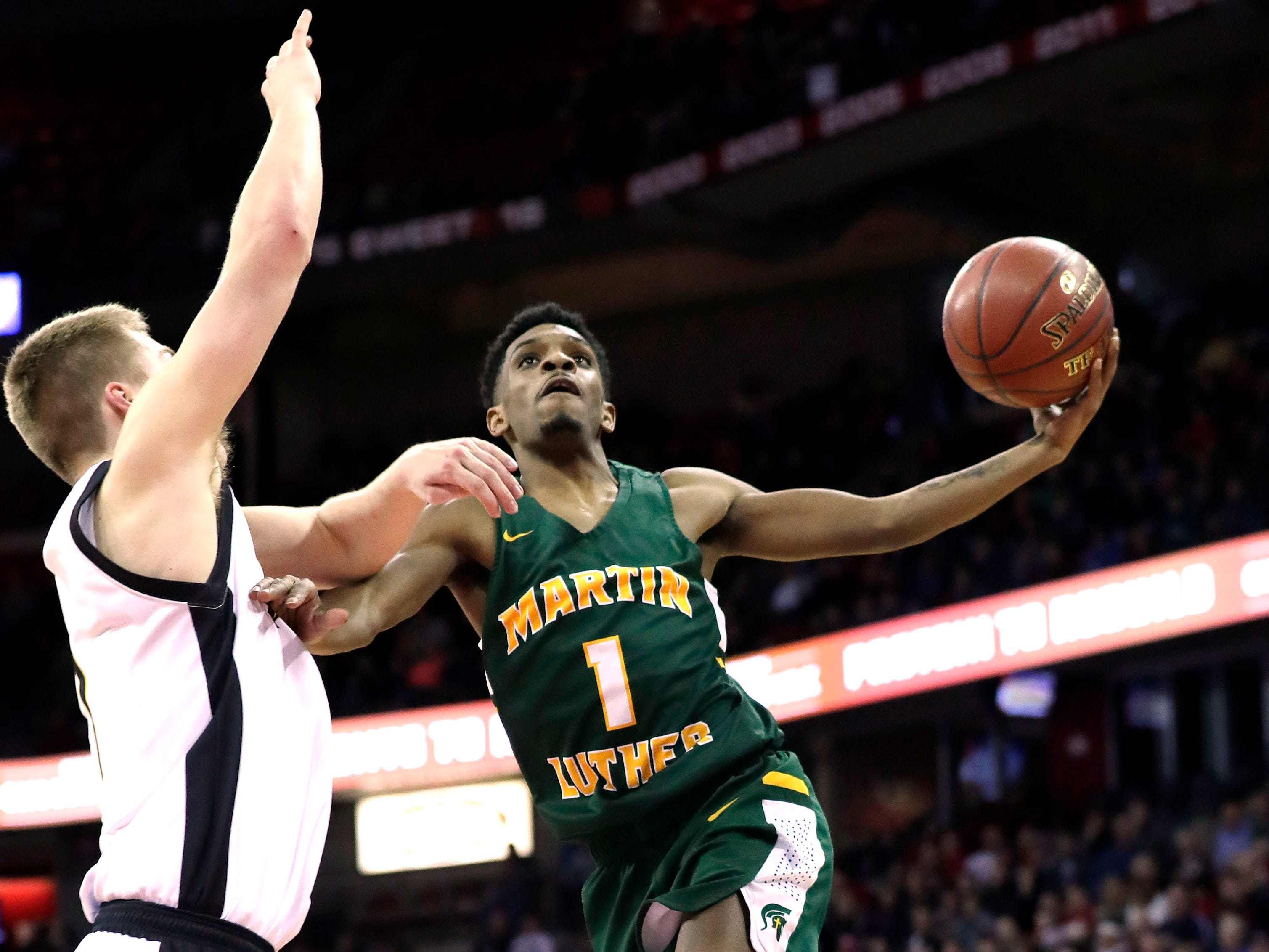 Martin Luther's Trequan Carrington is fouled by Waupun's Marcus Domask on a drive to the basket Saturday.