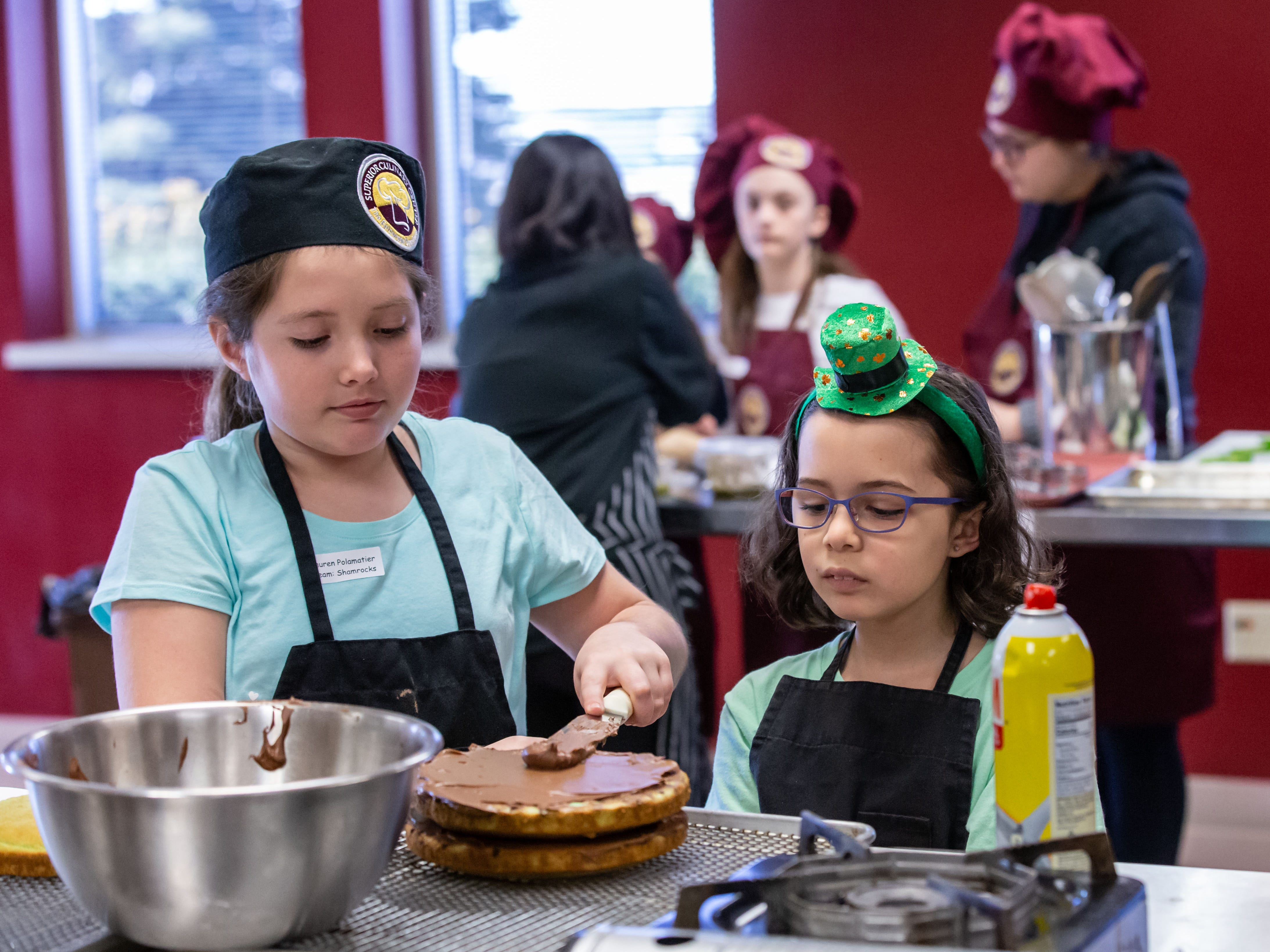 Chefs in training Lauren Polamatier (left), 10, and Mercedes Jaquez, 8, both of New Berlin, spread frosting on a cake they created during the St. Patrick's Kids Cooking Class at Superior Culinary Center in Saint Francis on Saturday, March 16, 2019. During the class youngsters learned how to prepare green pizza, Irish brown soda bread, guacamole and chips, mint chocolate chip cake and a vanilla mint milkshake.