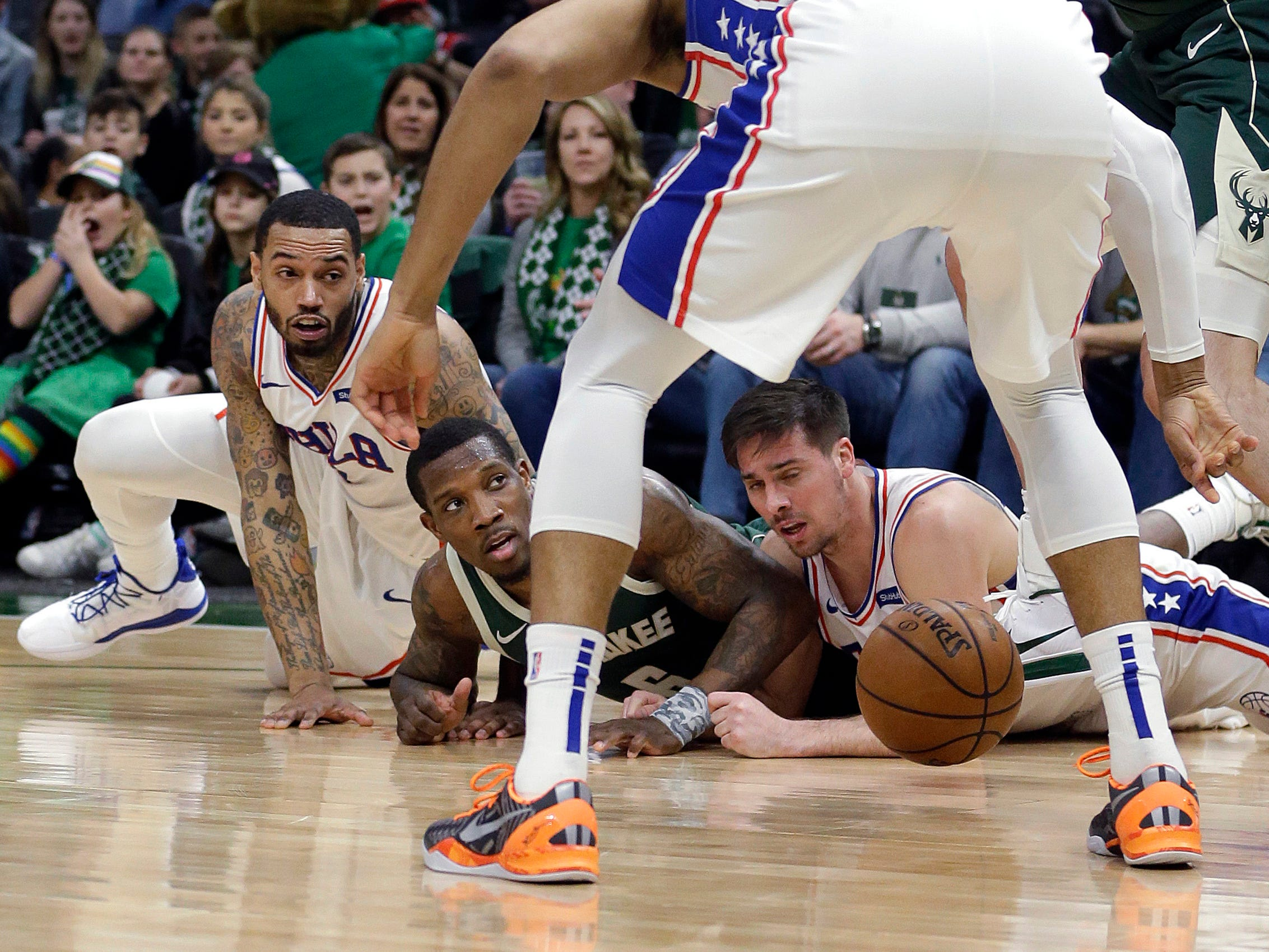 Bucks guards Eric Bledsoe goes to the floor along with Mike Scott (left) and T.J. McConnell of the 76ers in a scramble for a loose ball during the first half Sunday.